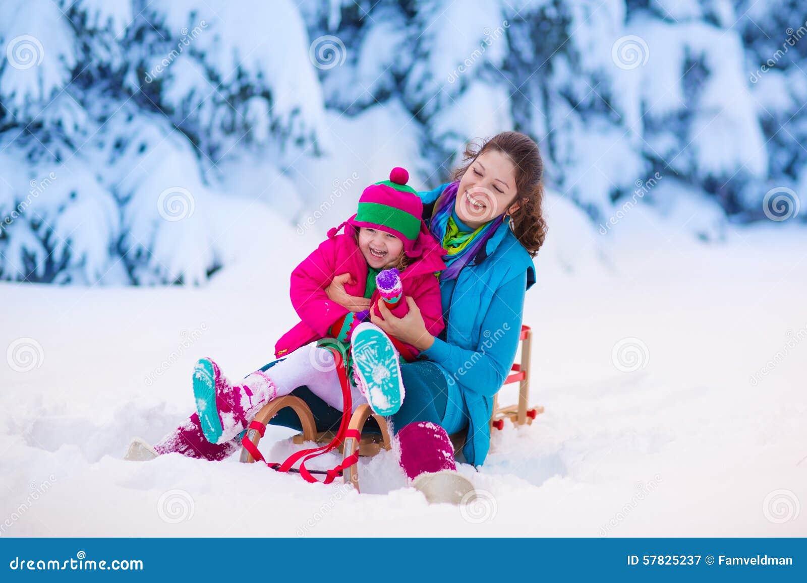 母亲和孩子sledding在一个多雪的公园