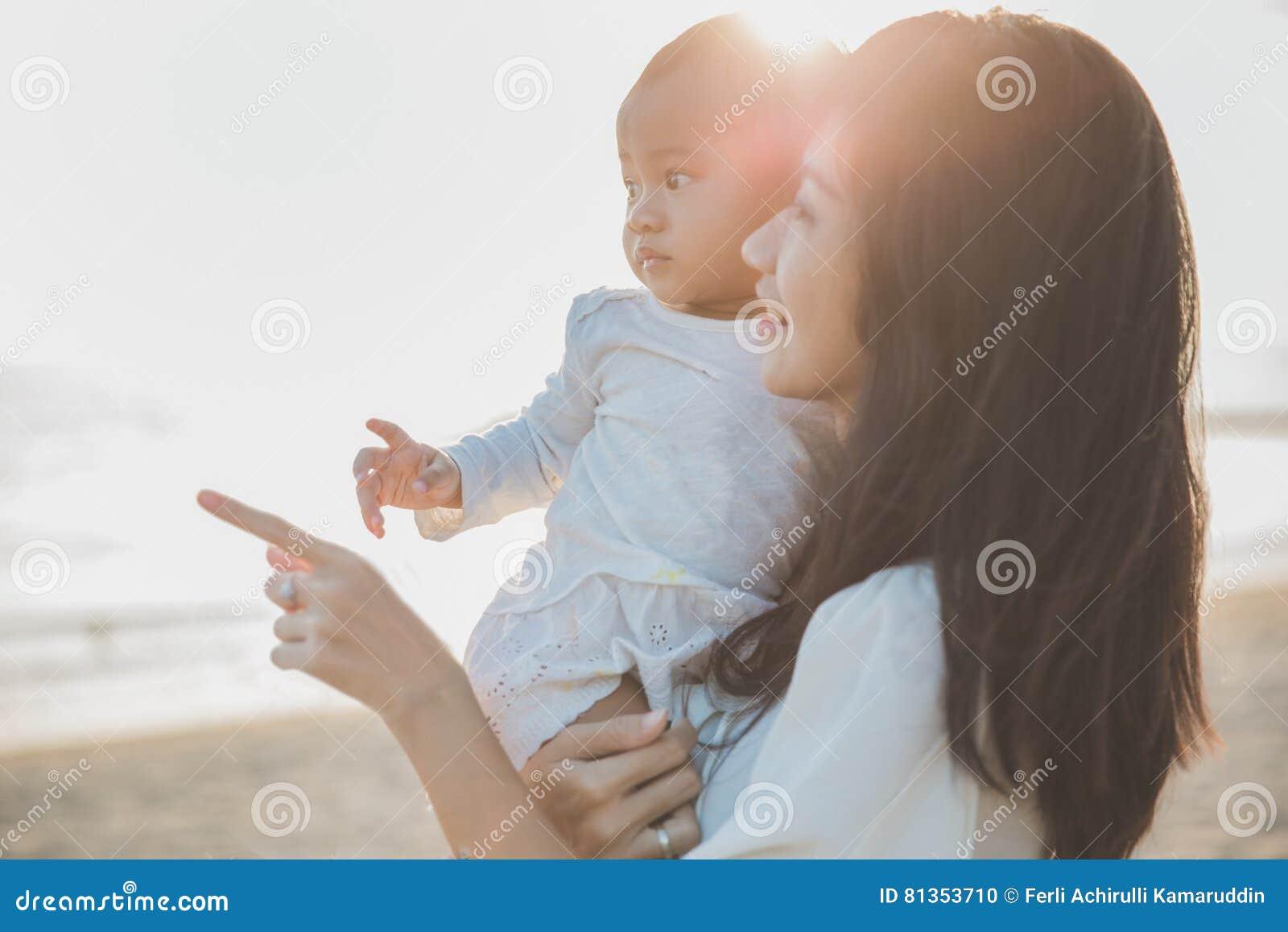 母亲和婴孩画象海滩的在日落