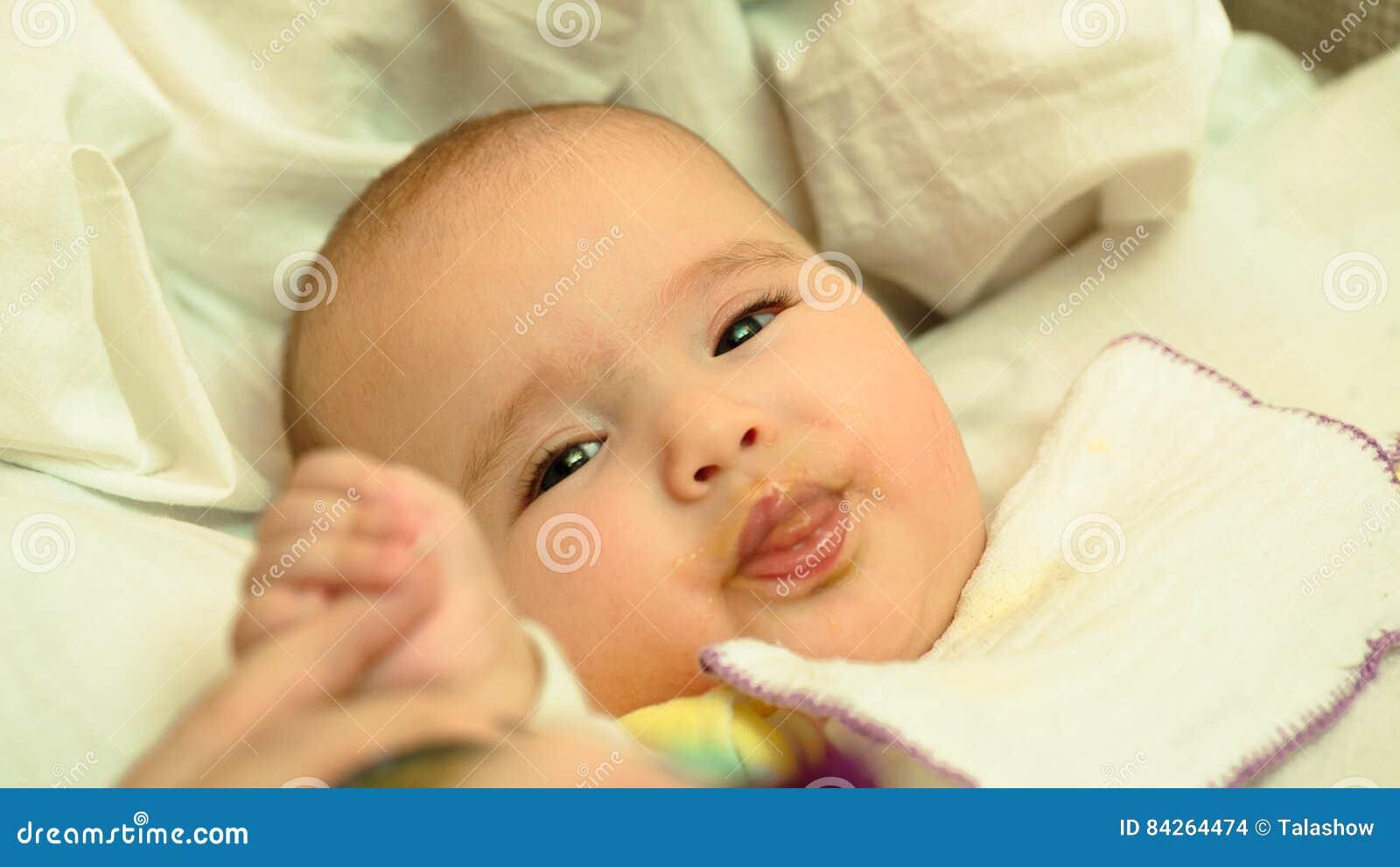 母亲哺养她的与匙子的小孩婴孩纯汁浓汤