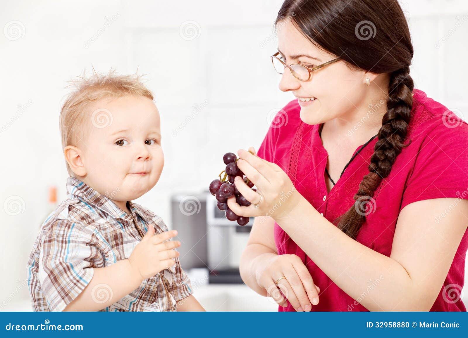 母亲哺养的孩子用葡萄