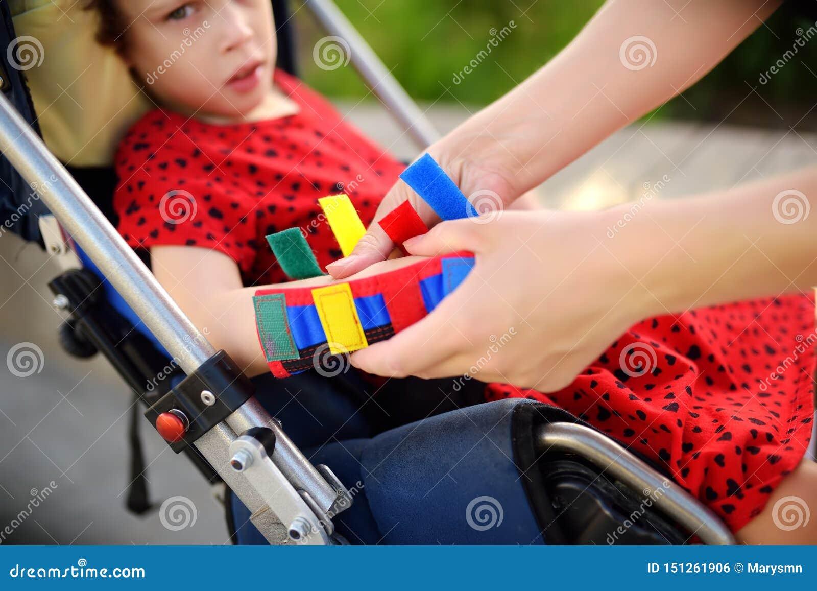 母亲在她的女儿胳膊投入整直法 残疾女孩坐轮椅 儿童大脑麻痹