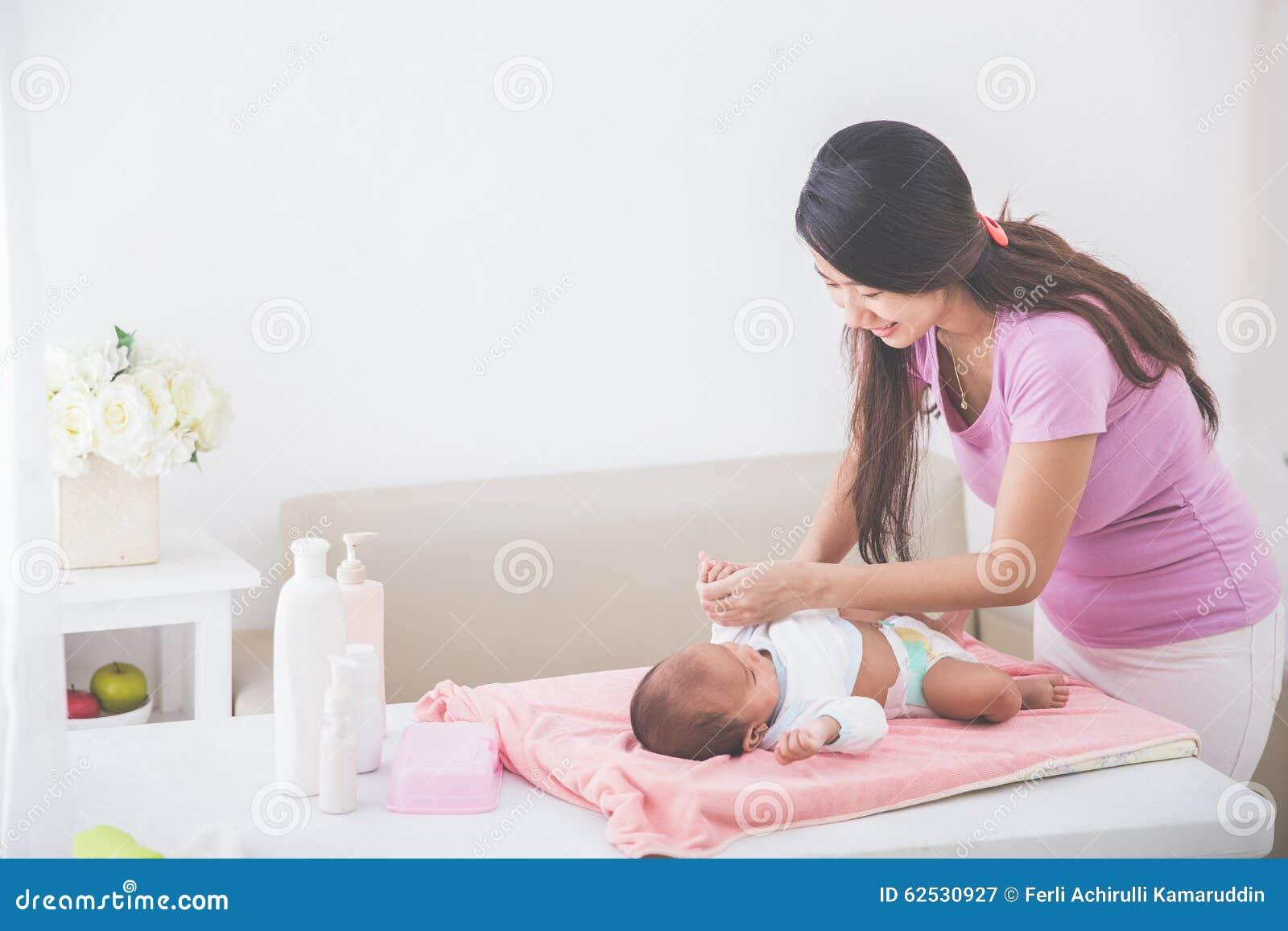 母亲投入了一些衣裳给她的婴孩