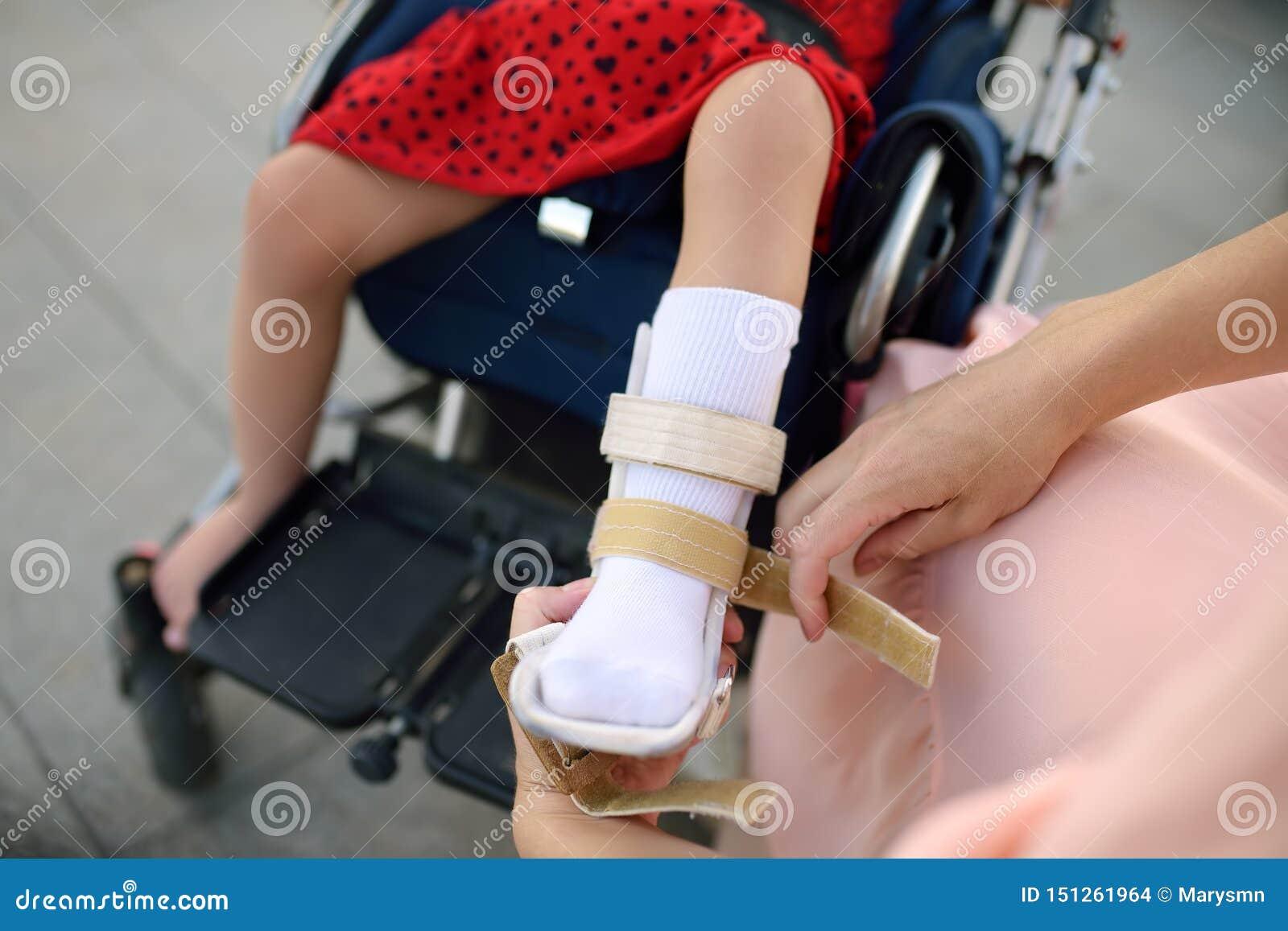 母亲投入整直法她的女儿腿 残疾女孩坐轮椅 儿童大脑麻痹