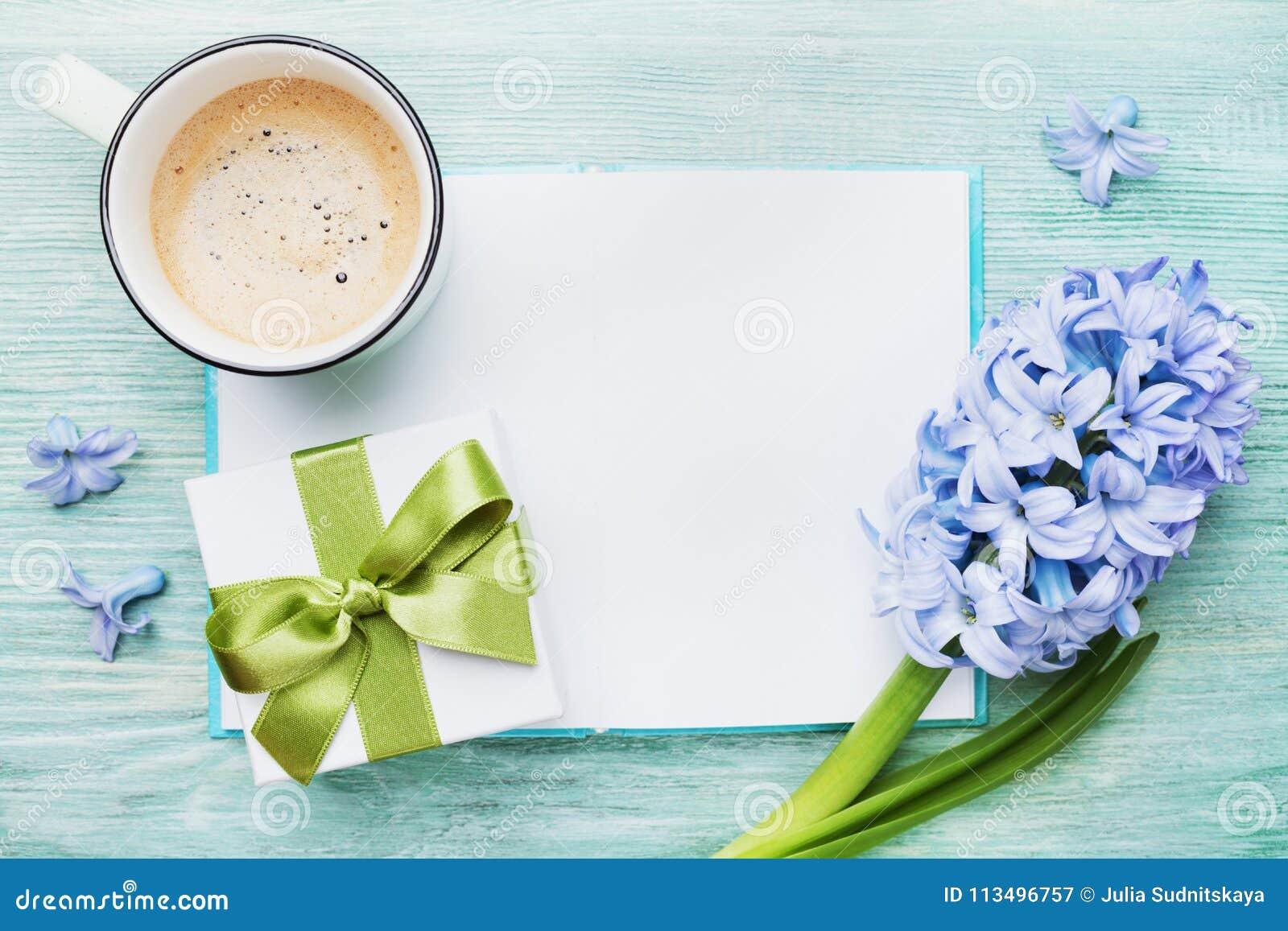 母亲节春天与空的笔记本的假日卡片与咖啡的招呼的文本的、礼物或者当前箱子和风信花开花