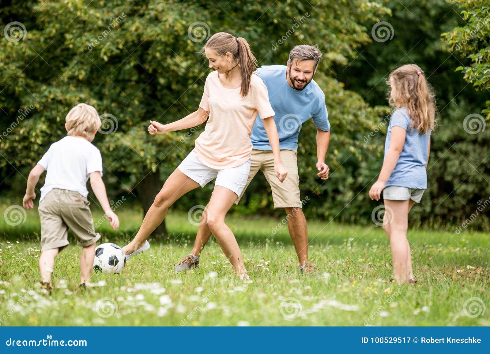 母亲踢与家庭的橄榄球足球
