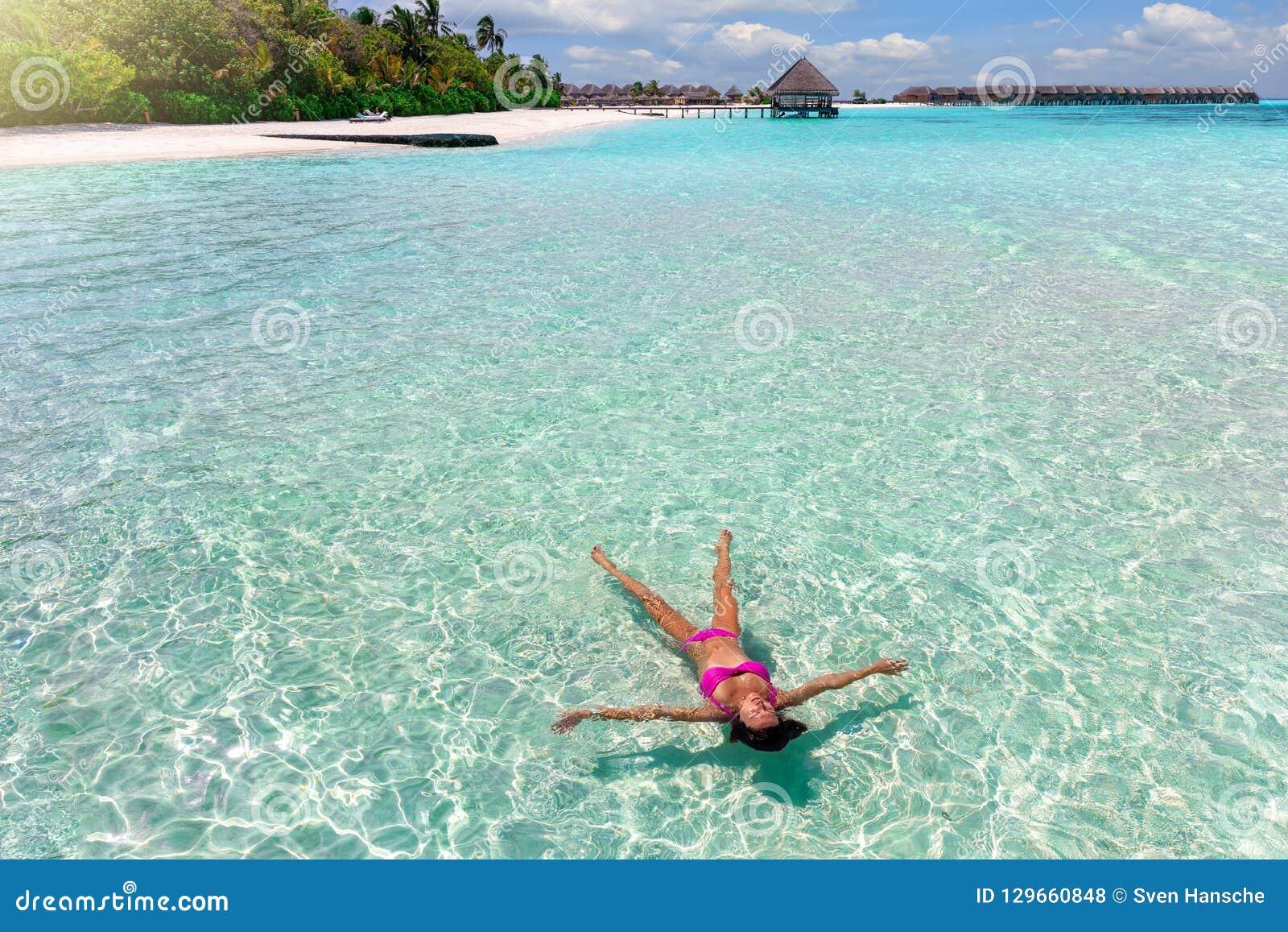 比基尼泳装浮游物的妇女在绿松石,马尔代夫的热带海