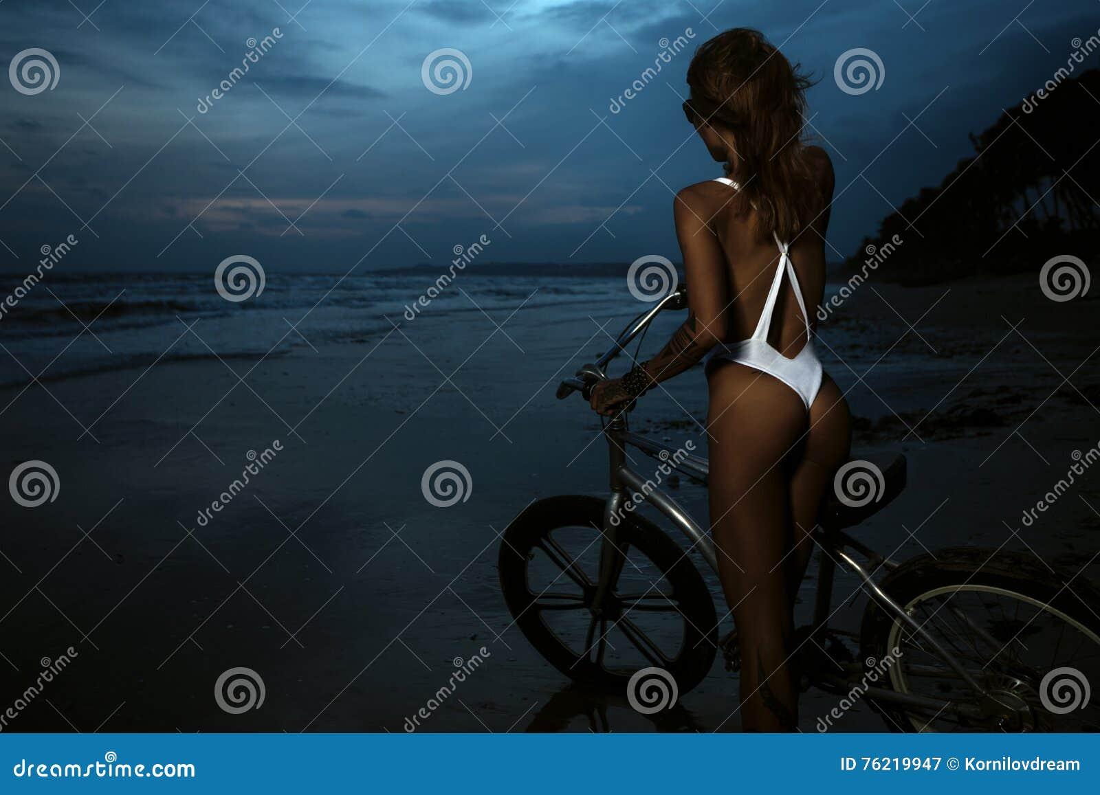 比基尼泳装的妇女有她的自行车的