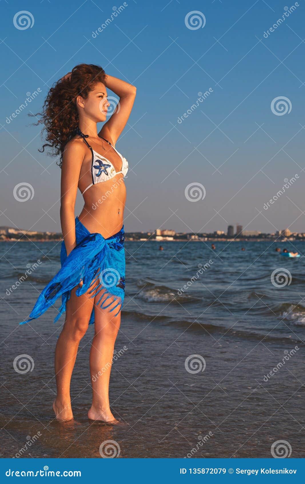 比基尼泳装的年轻美丽的亭亭玉立的被晒黑的妇女在海滩调查距离