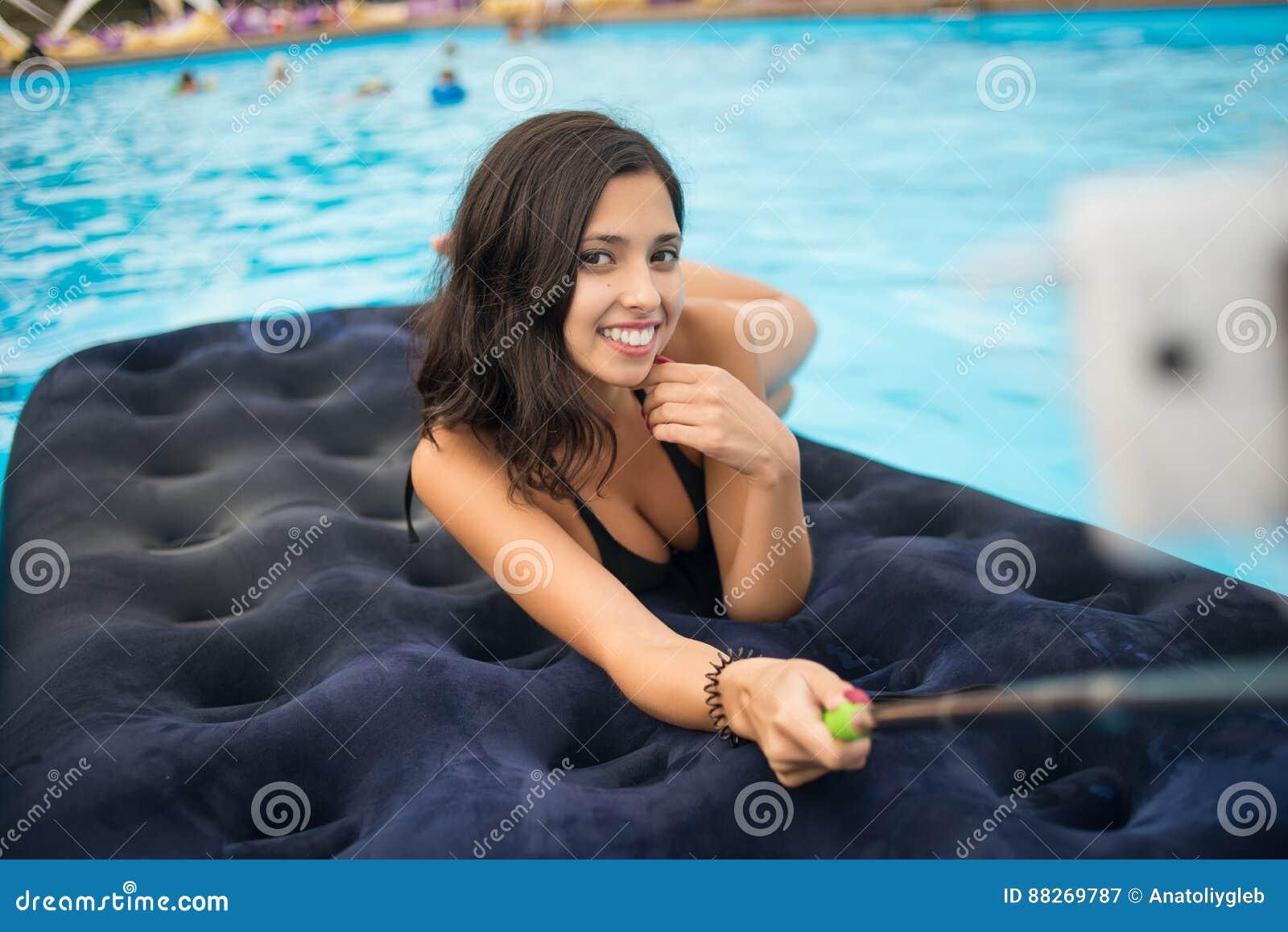 比基尼泳装的微笑的女性和在电话做selfie照片用在一个床垫的selfie棍子在水池在手段