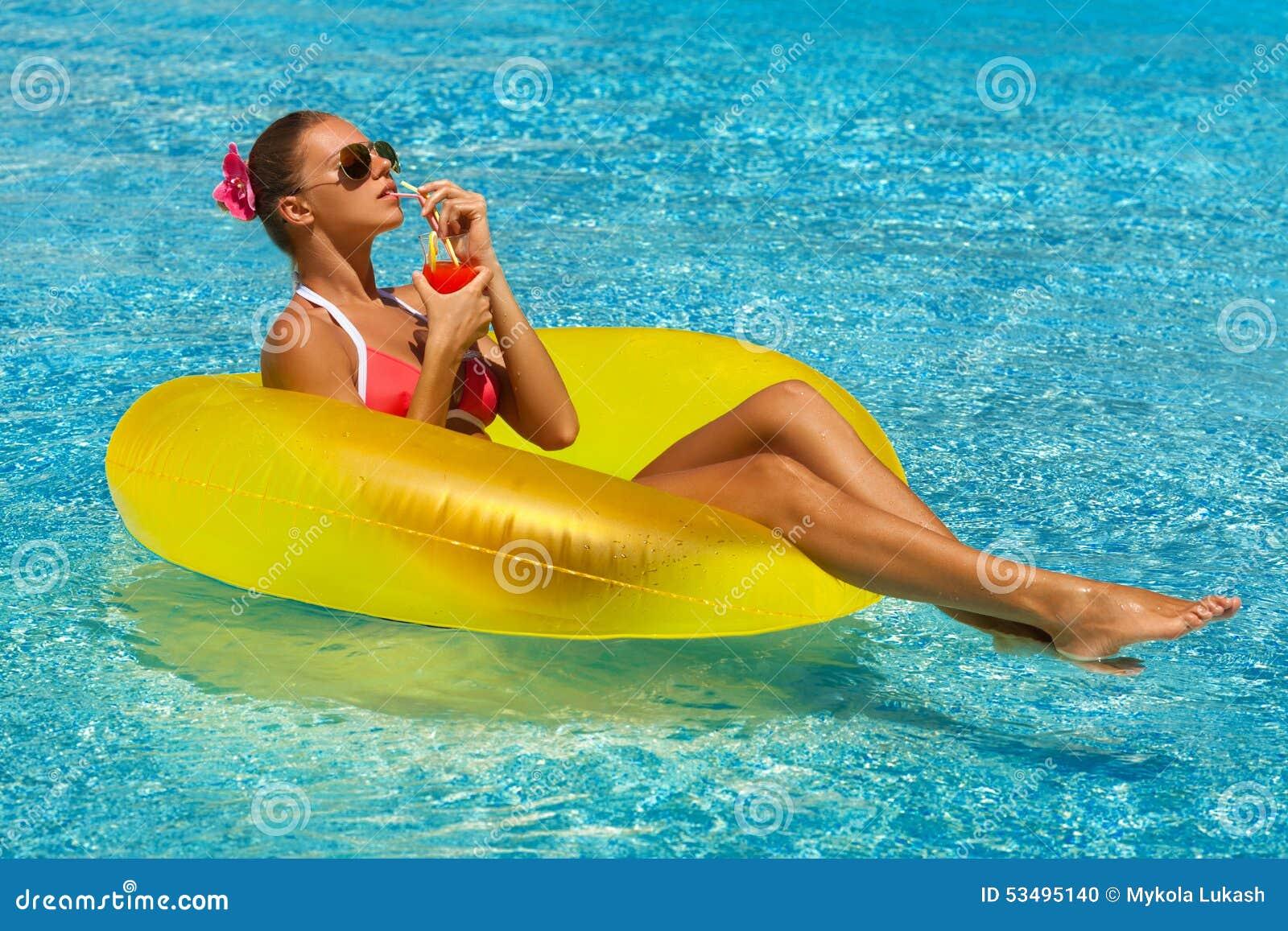比基尼泳装的性感的妇女享用夏天太阳和晒黑在水池的假日期间的与鸡尾酒
