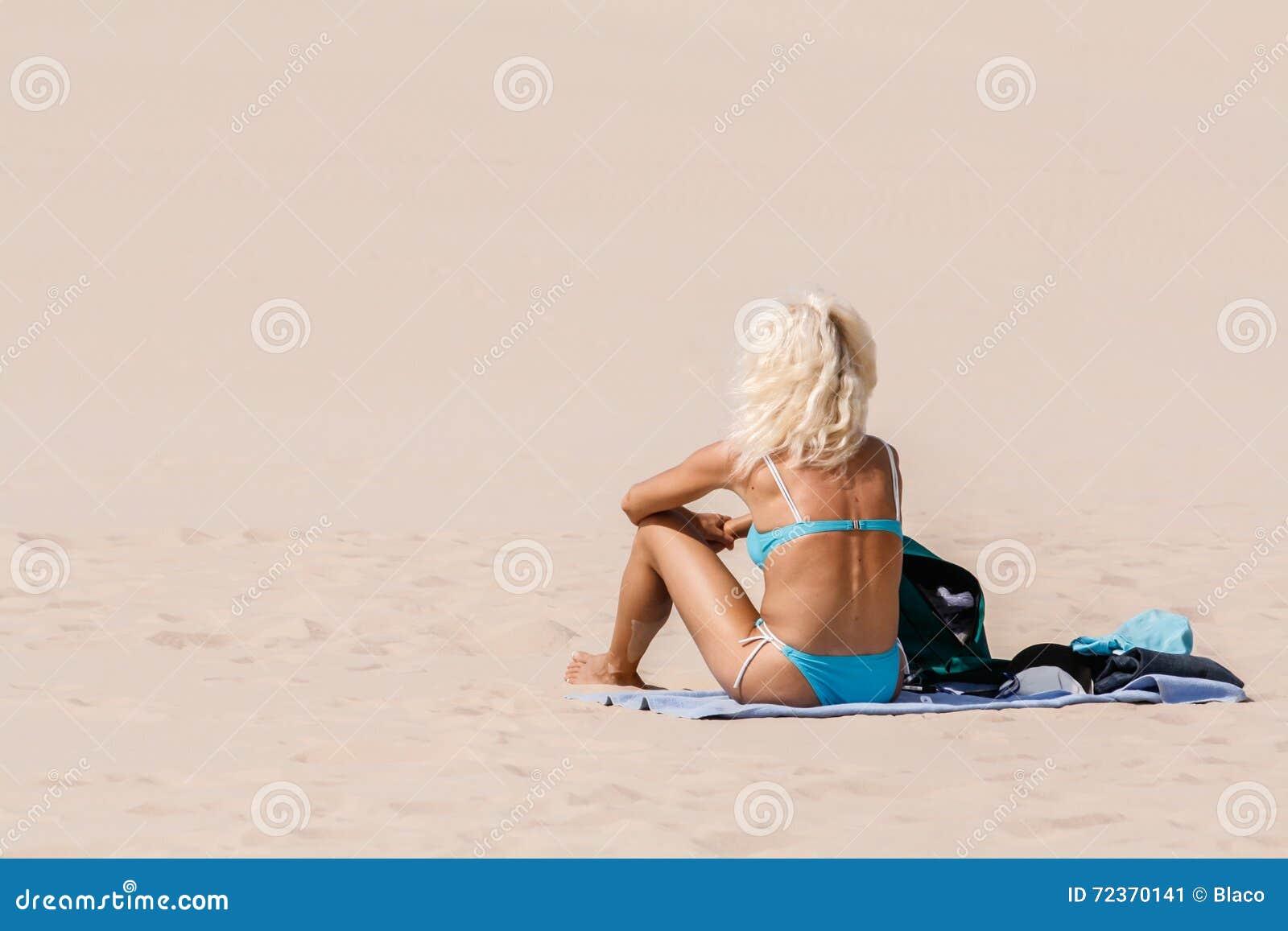 比基尼泳装选址的妇女在沙子
