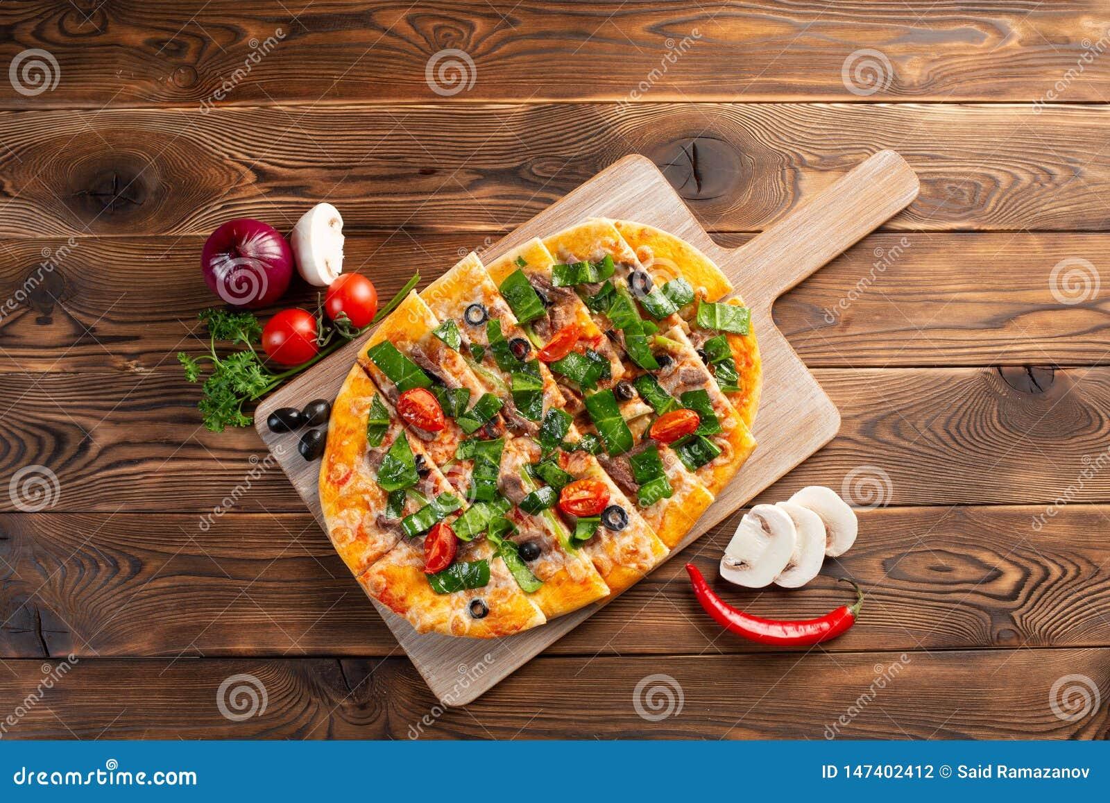 比萨用小牛肉和干蕃茄在木背景
