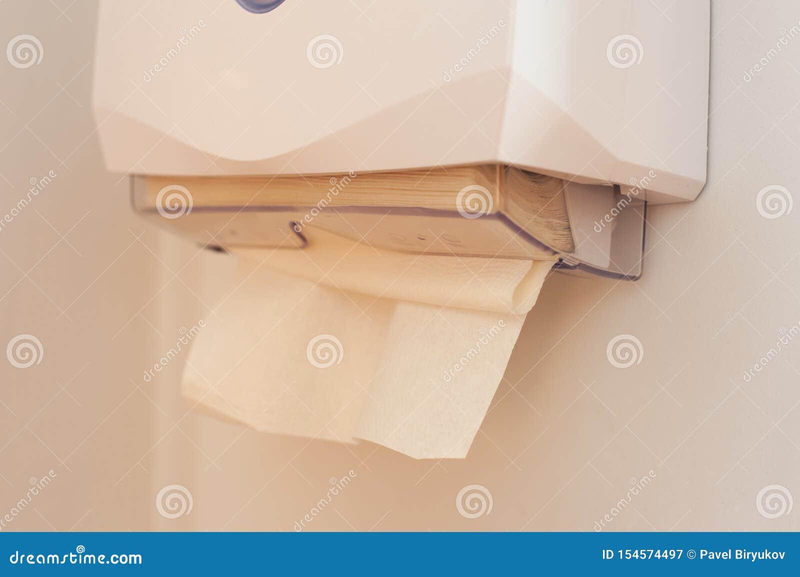毛巾纸特写镜头在垂悬在墙壁上的分配器的