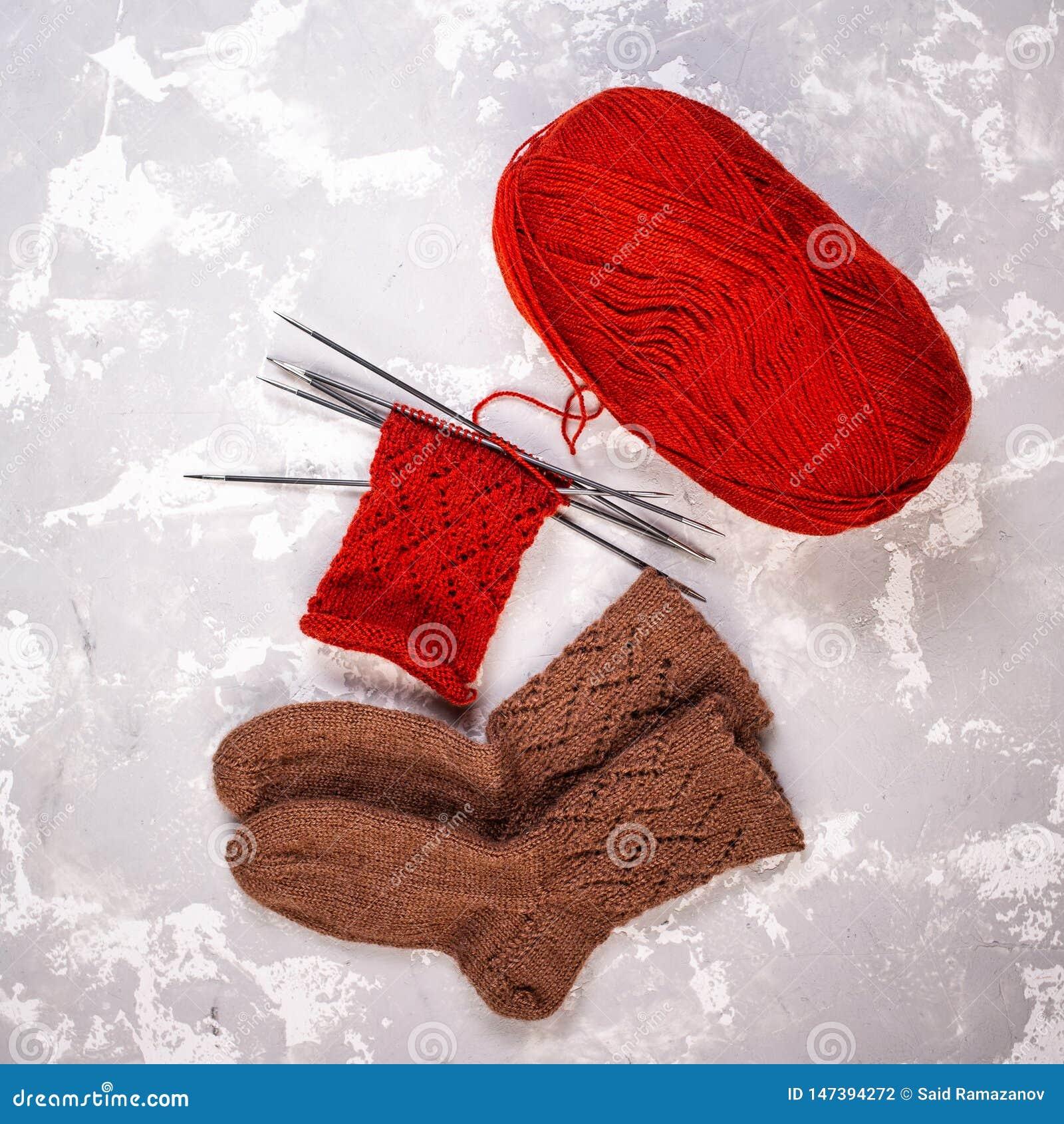 毛线、编织针和被编织的袜子球在灰色水泥背景
