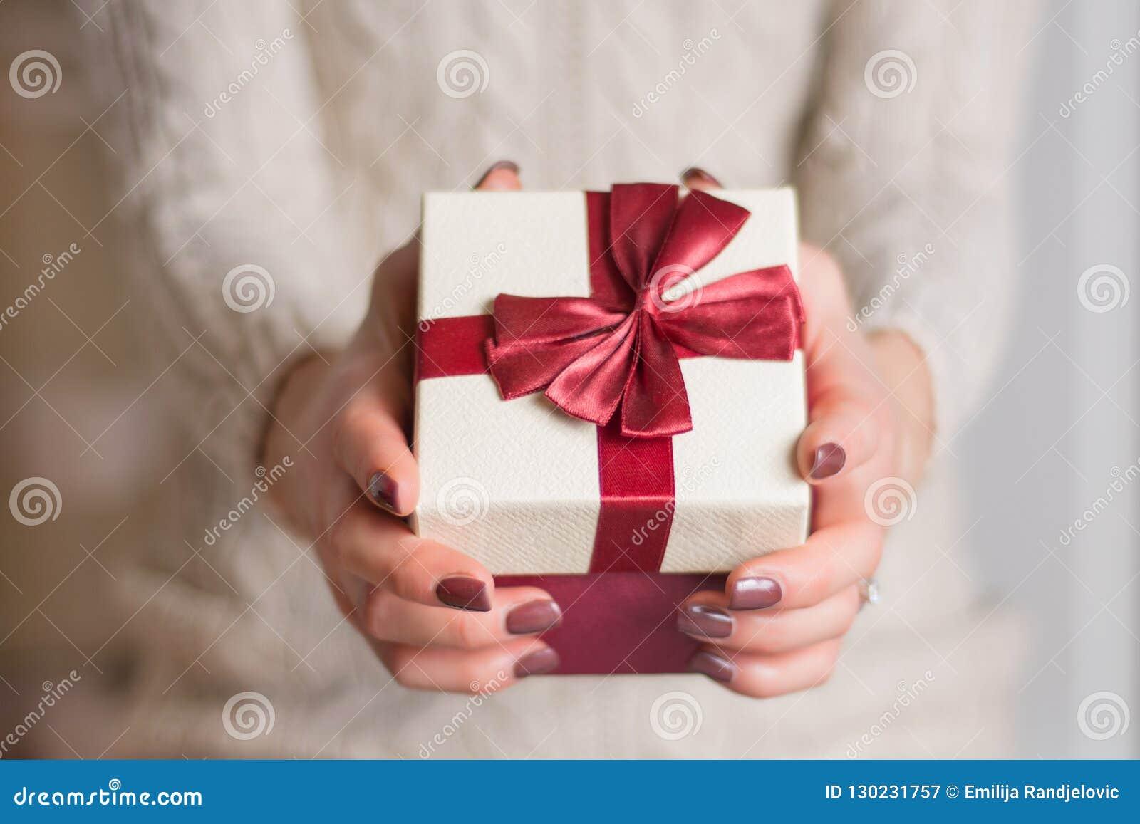 毛线衣藏品礼物盒的女孩有红色丝带领带弓的