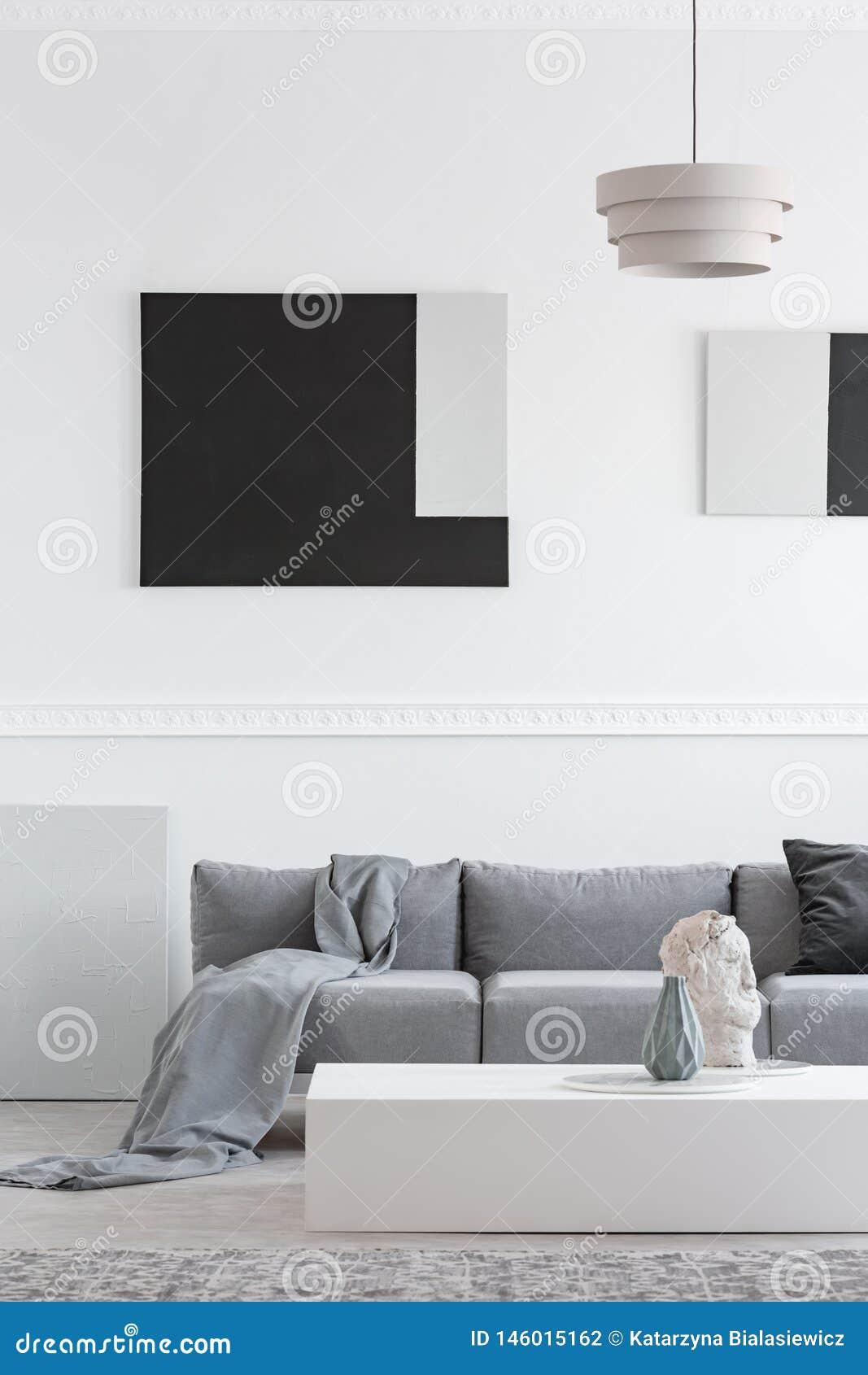 毯子和黑枕头在舒适的沙发在时髦的客厅内部