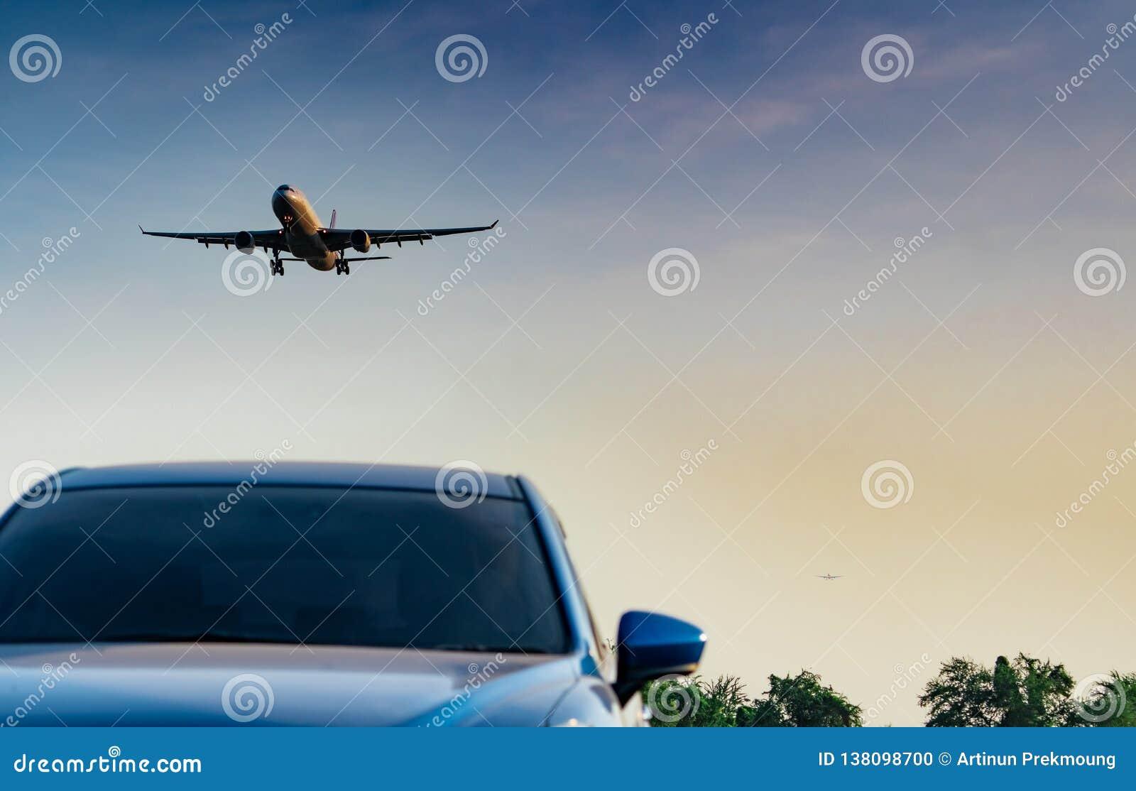 民航 客机接进着陆蓝色SUV汽车在有天空蔚蓝和云彩的机场在日落 到来飞行
