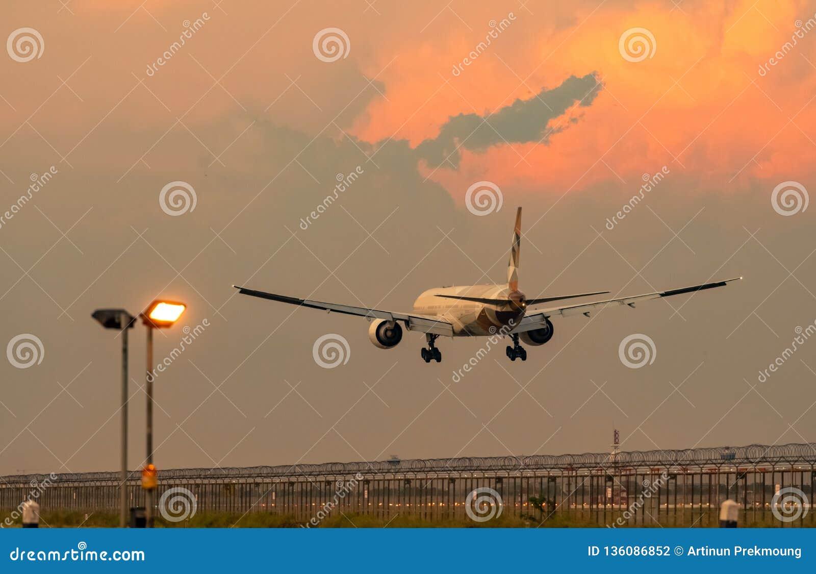 民航 客机着陆在有美丽的日落天空和云彩的机场 到来飞行 飞机飞行