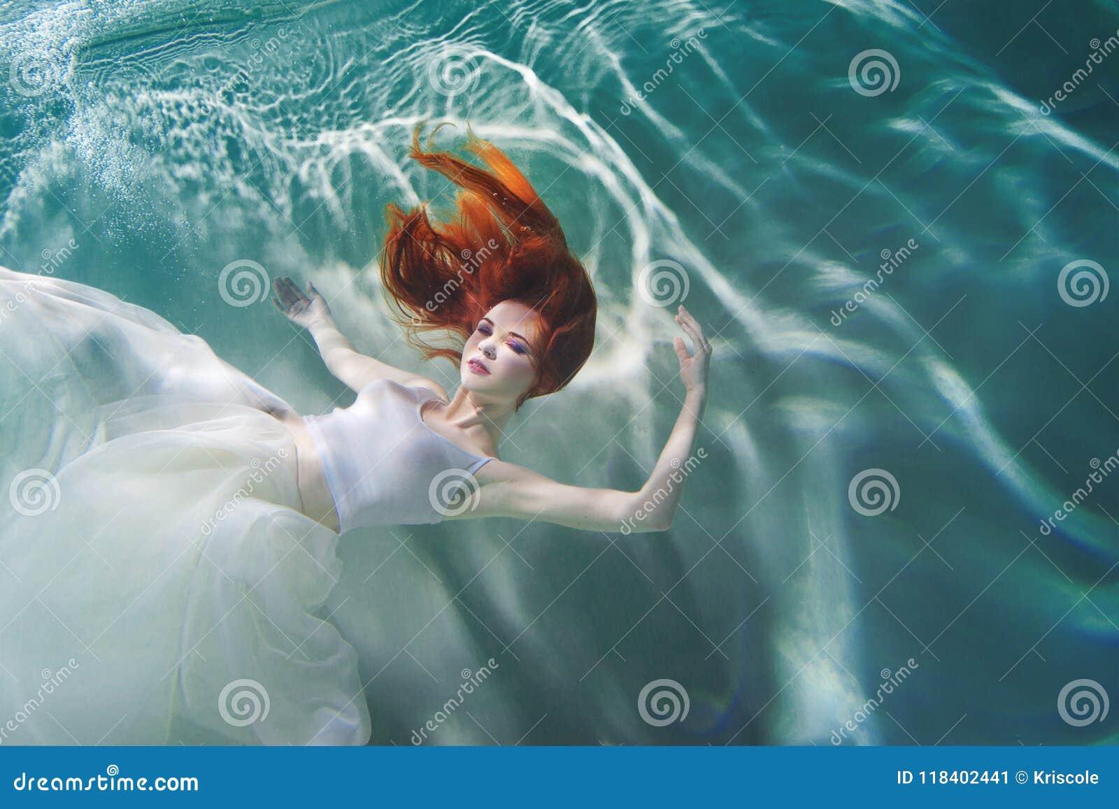 水下的女孩 一件白色礼服的美丽的红发妇女,游泳在水下