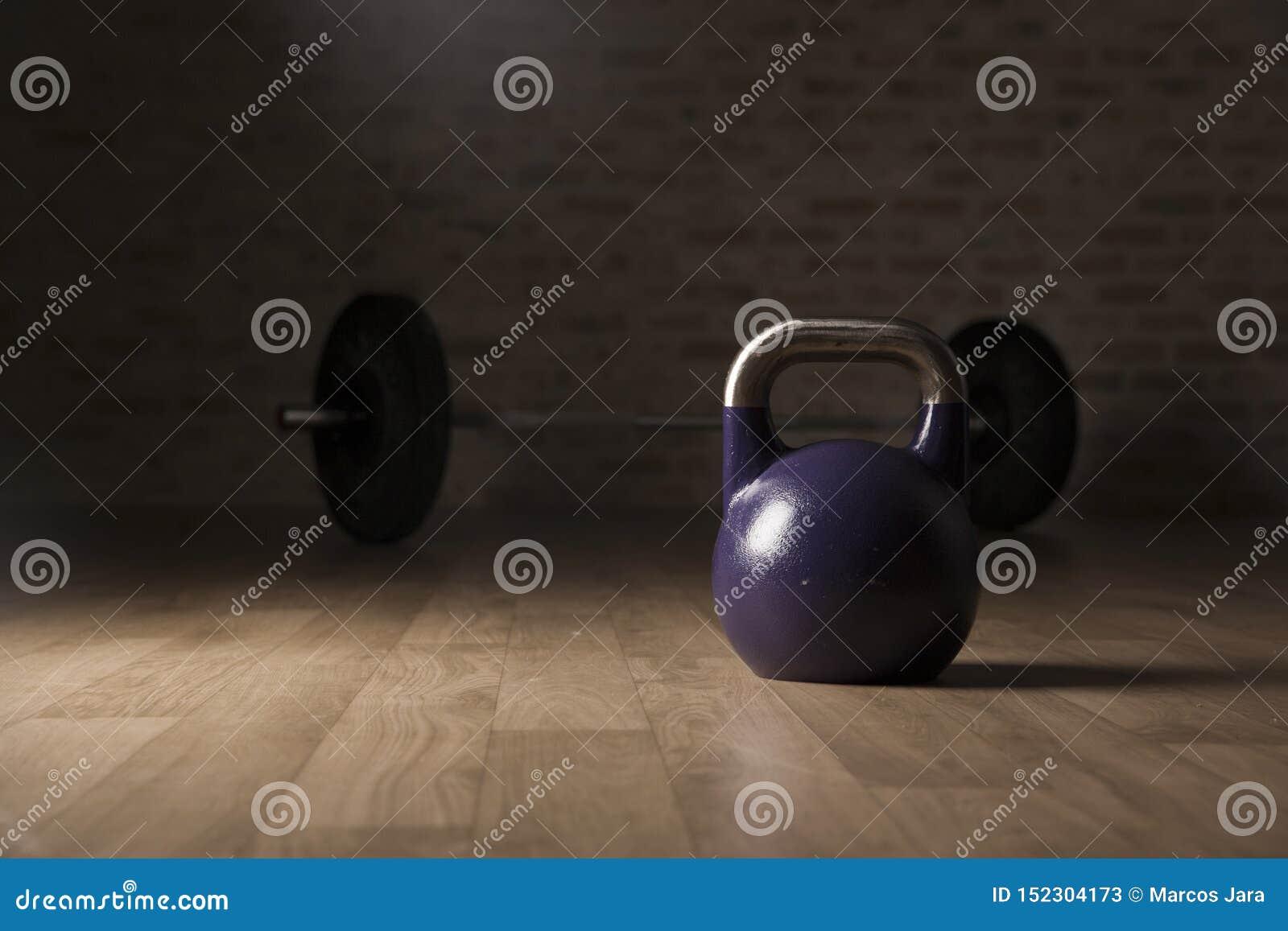 水壶响铃和举重酒吧在一间木地板健身房