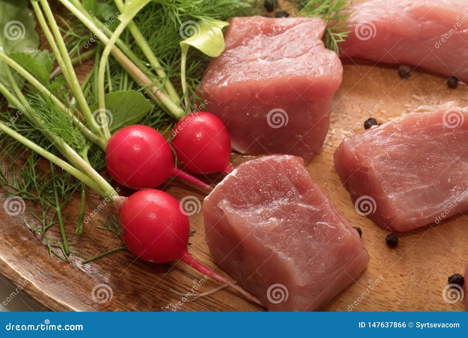 水多的肉片在有调味料、草本和菜的一块木板材服务