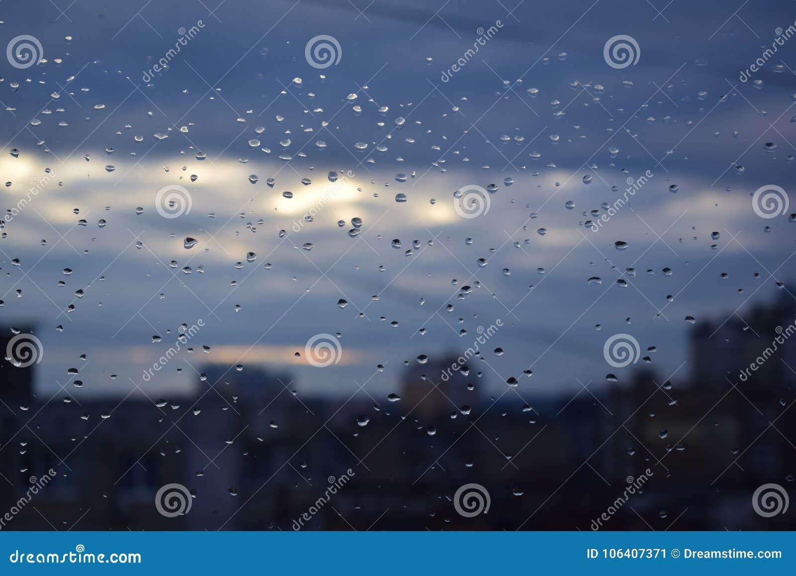 水小滴在一块玻璃的在城市和天空背景