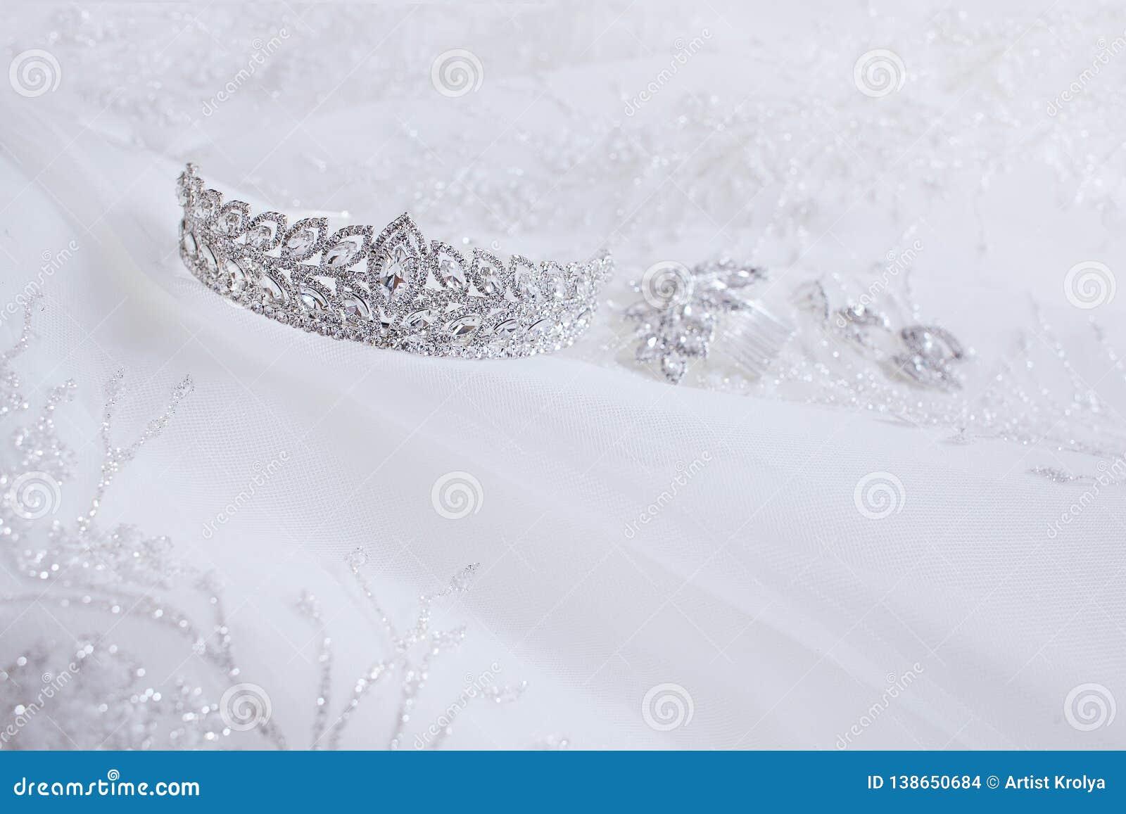 水晶首饰:耳环,簪子,在白色婚姻的背景的王冠