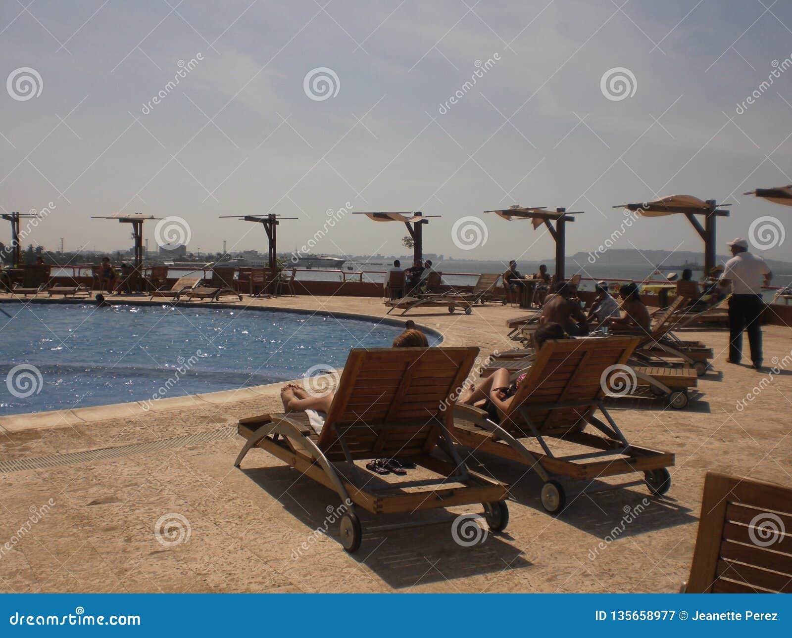 水池和sunbeds看法与晒日光浴在加勒比的旅馆里的沐浴者