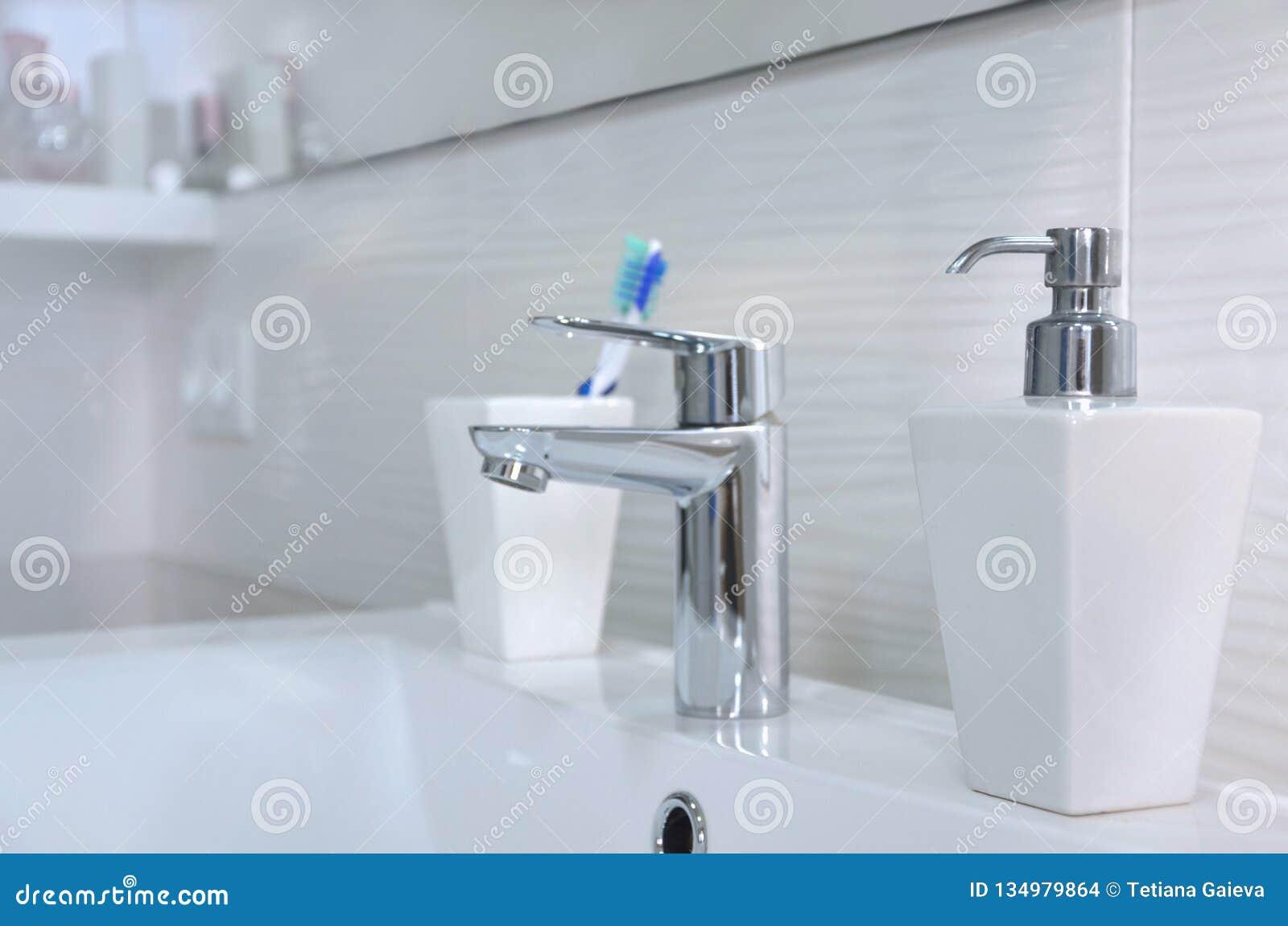 水盆在白色卫生间、肥皂分配器和牙刷里在玻璃