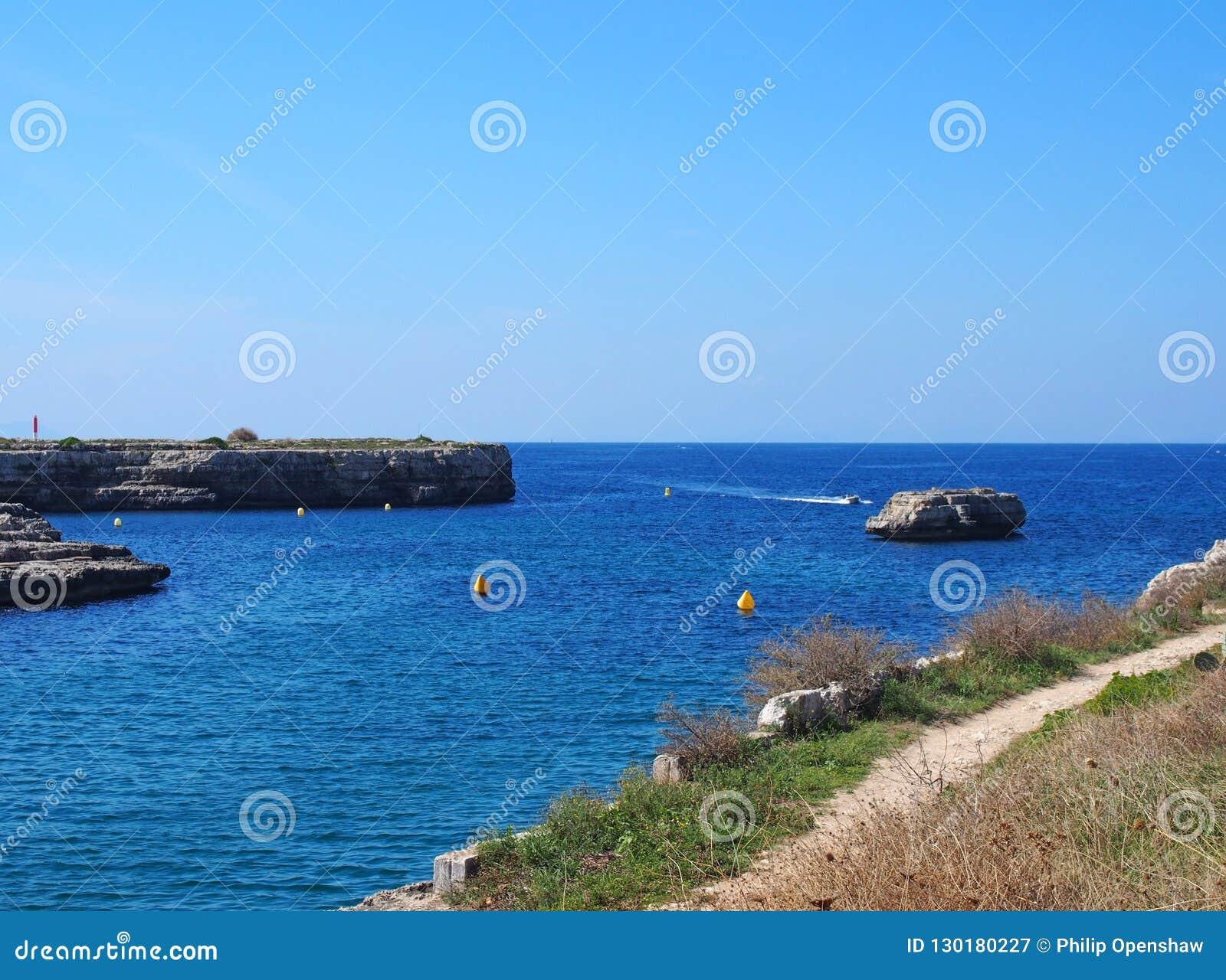 水芋属Des Degeledor风景看法在Ciutadellawith俯视与蓝色被日光照射了海和快艇的clifftop道路海湾