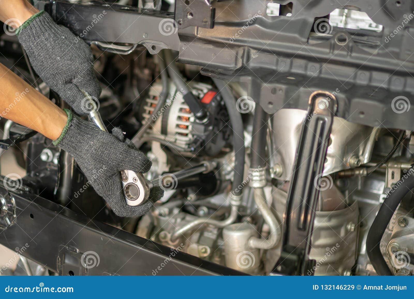 汽车机械师的手有板钳的 汽车修理