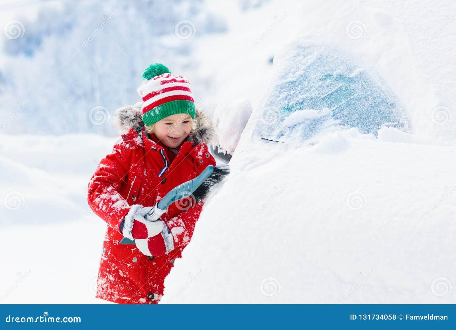 汽车的儿童掠过的雪在风暴以后 与冬天刷子的孩子和刮板清洁在隔夜雪飞雪以后的家用汽车