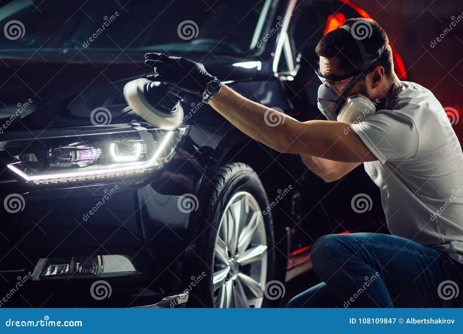 汽车详述-有轨道磨光器的人在汽车修理店 选择聚焦