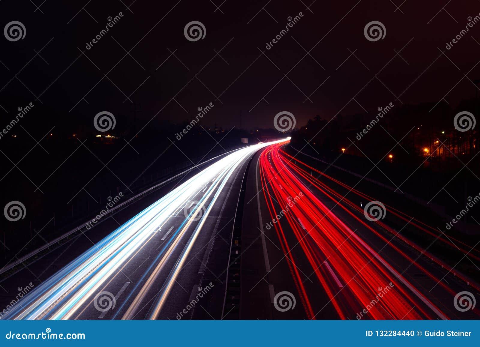 汽车轻的足迹在高速公路的晚上