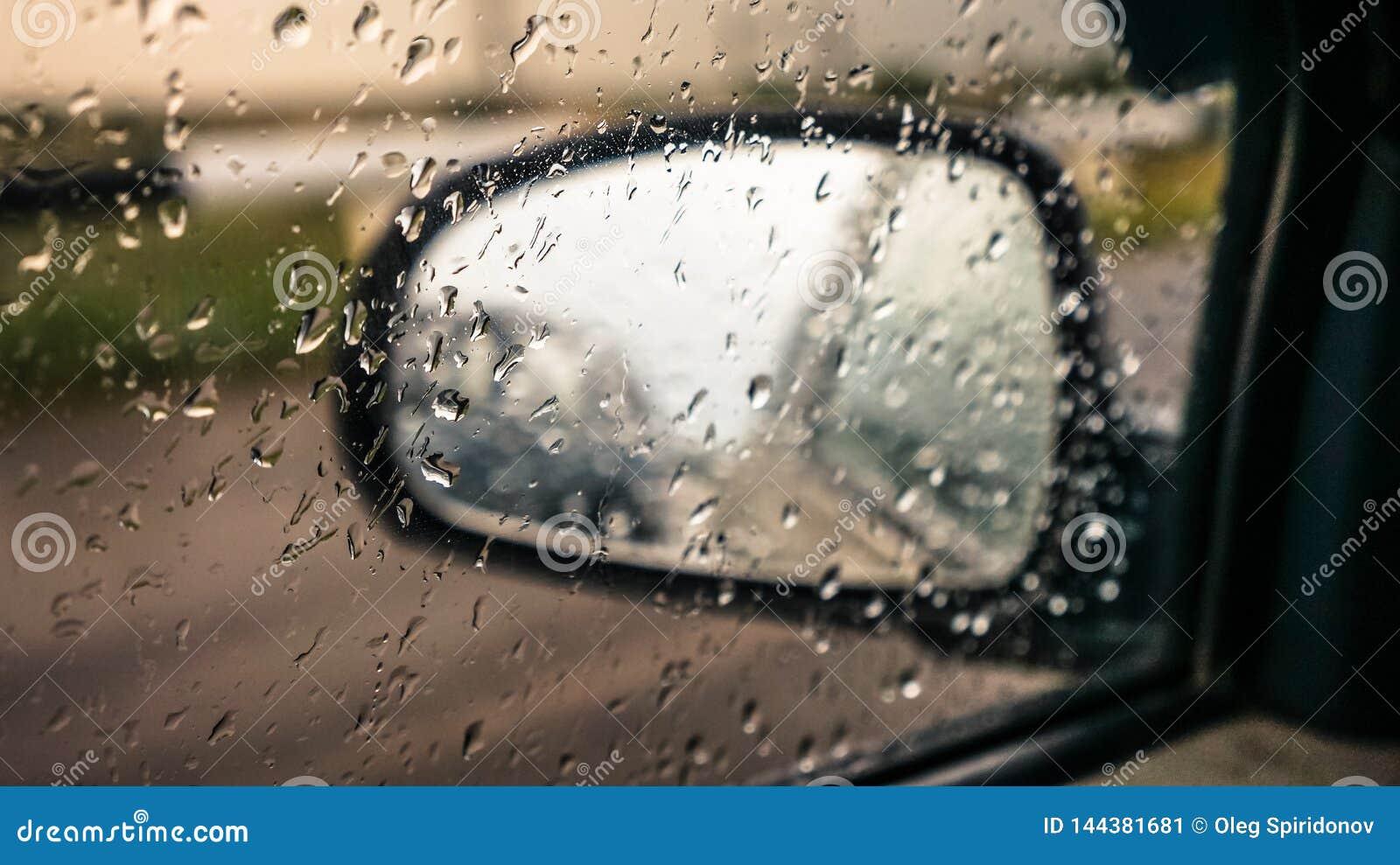 汽车镜子通过与雨珠的玻璃