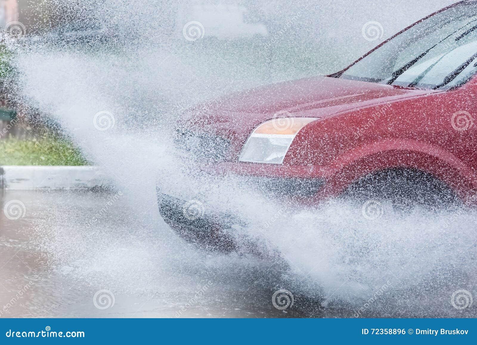 汽车飞溅水的雨水坑