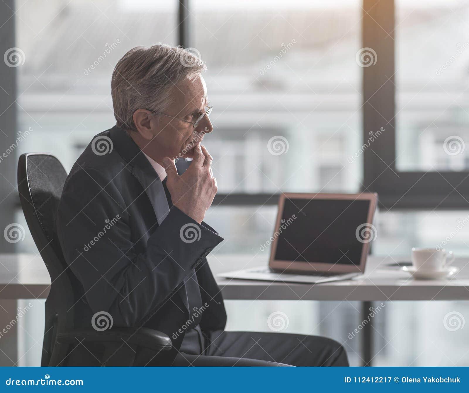 沉思老商人与膝上型计算机一起使用