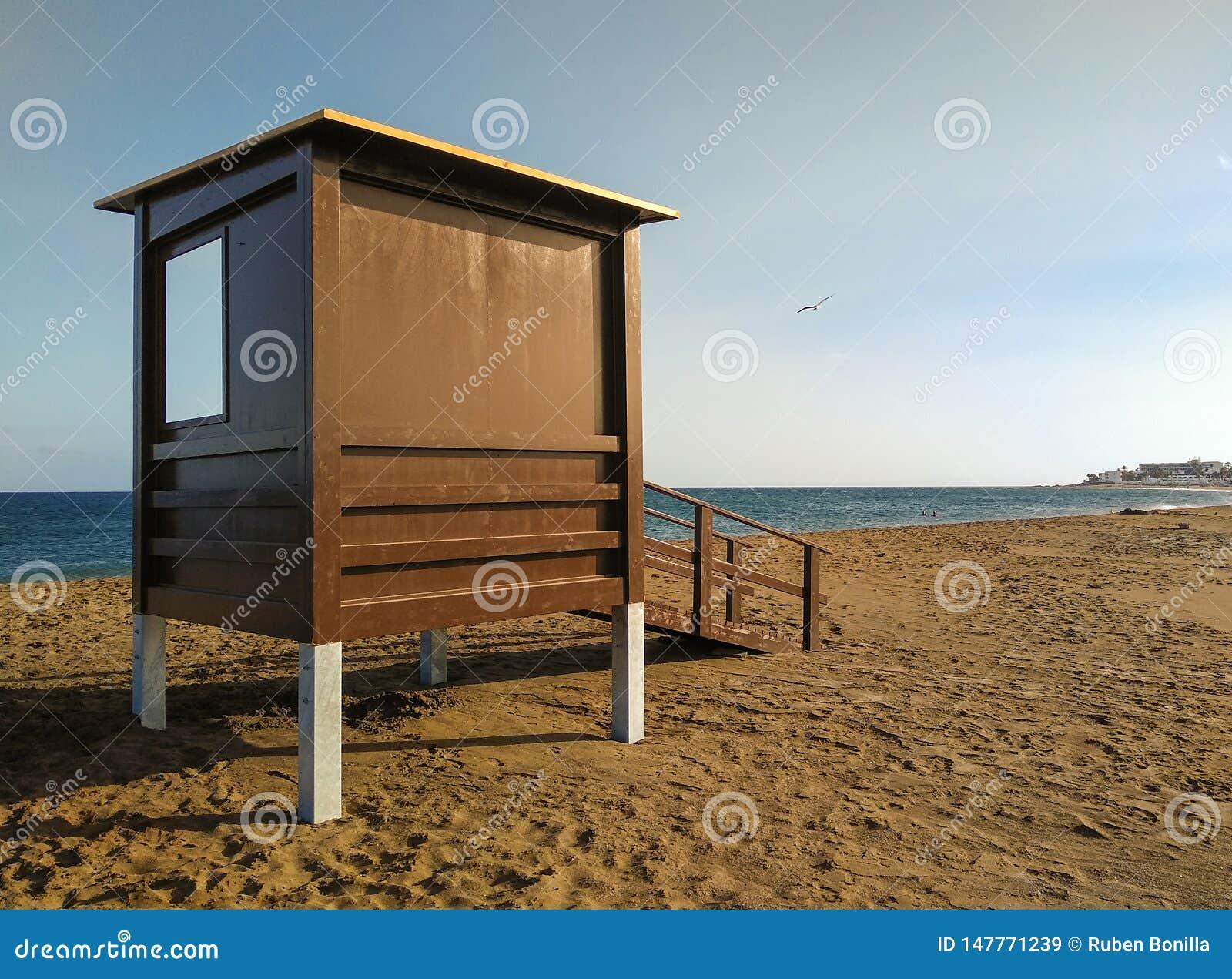 沙子的救生员房子在没有卫兵或人游泳的一个平安的海滩在日落小时 在救生员驻地后