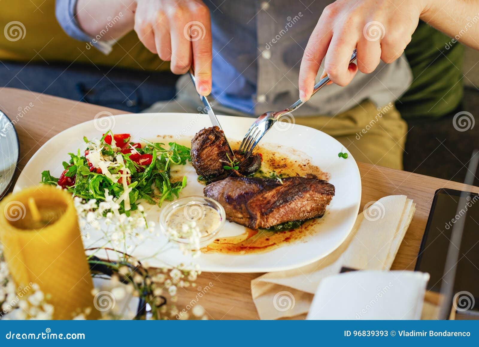 沙拉用在一块板材的肉,在一张木桌上 有叉子和刀子的,裁减肉男性手