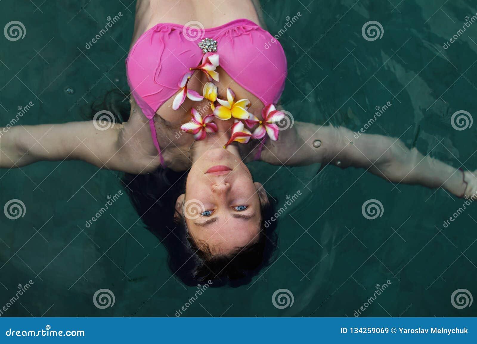 没有化妆用品,有羽毛花的美丽的年轻女人的自然女孩在蓝色游泳场