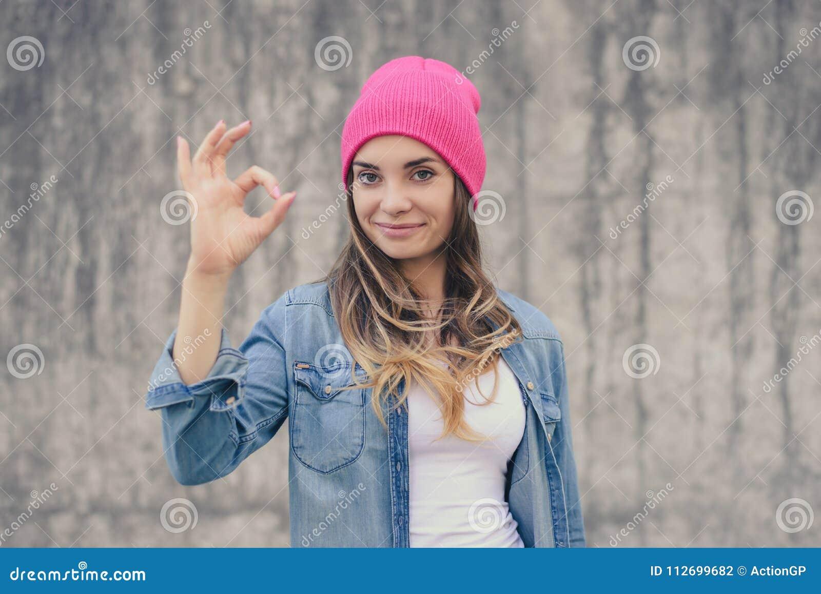 没有构成的愉快的确信的微笑的妇女在牛仔裤衬衣,白色帽子穿戴了,有长卷曲的听见显示好标志反对灰色