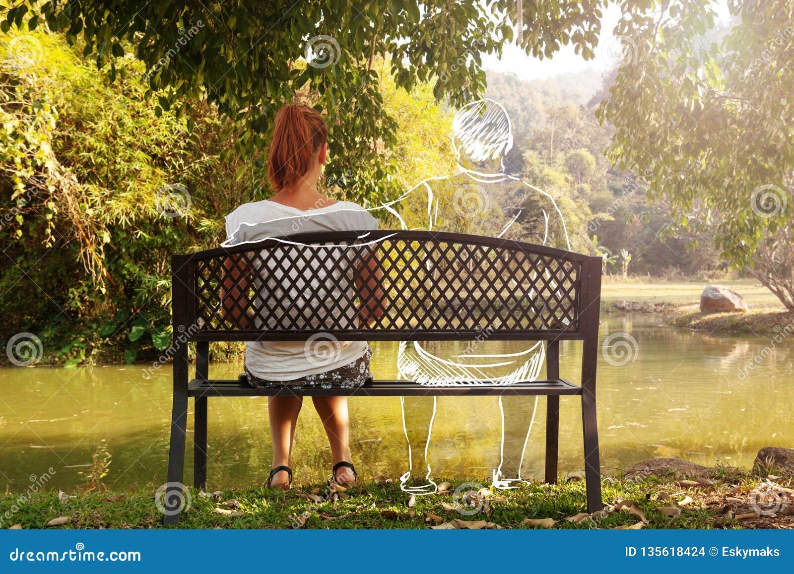 沮丧和哀伤的年轻女人单独坐长凳在公园