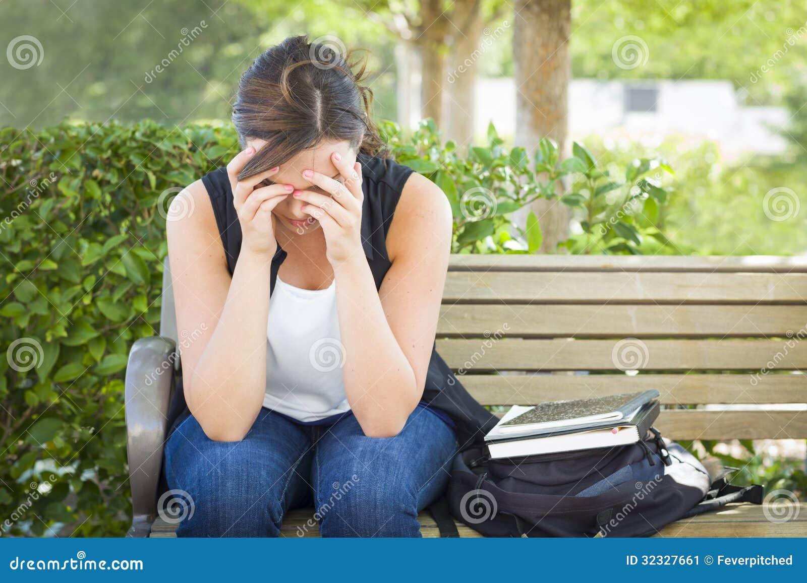 沮丧的少妇单独坐长凳在书旁边