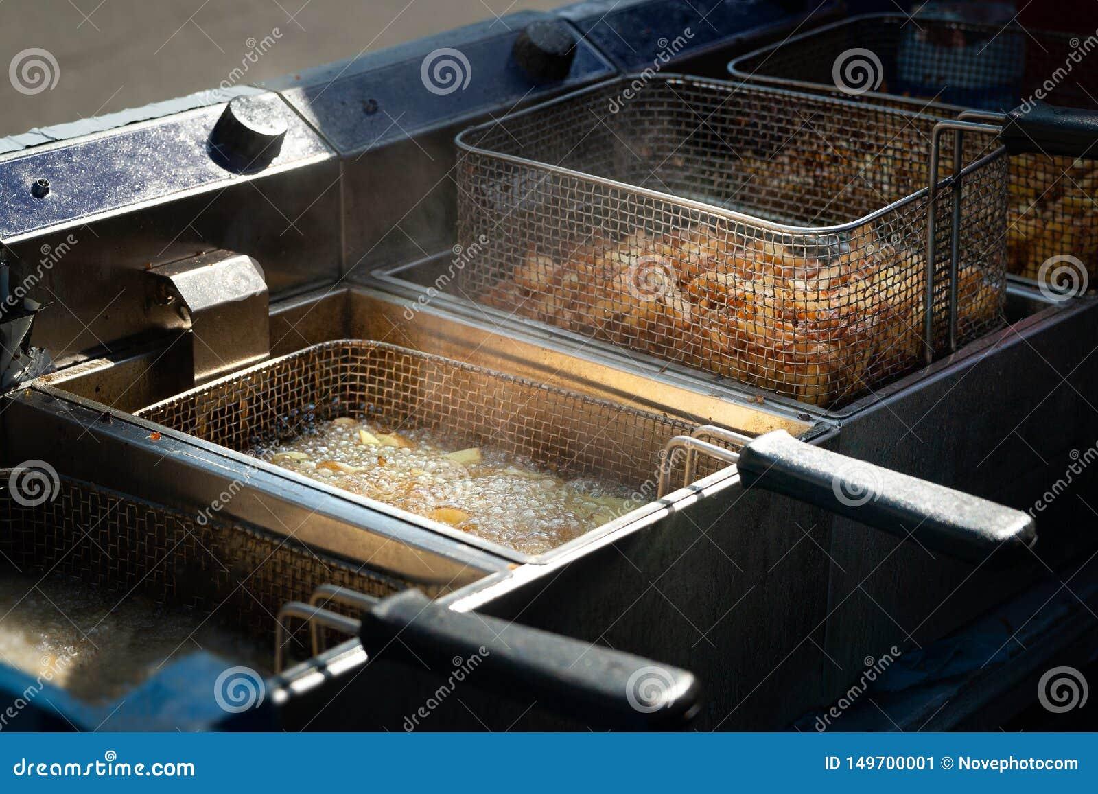 油炸土豆 在炸锅的煮沸的油油煎的薯条