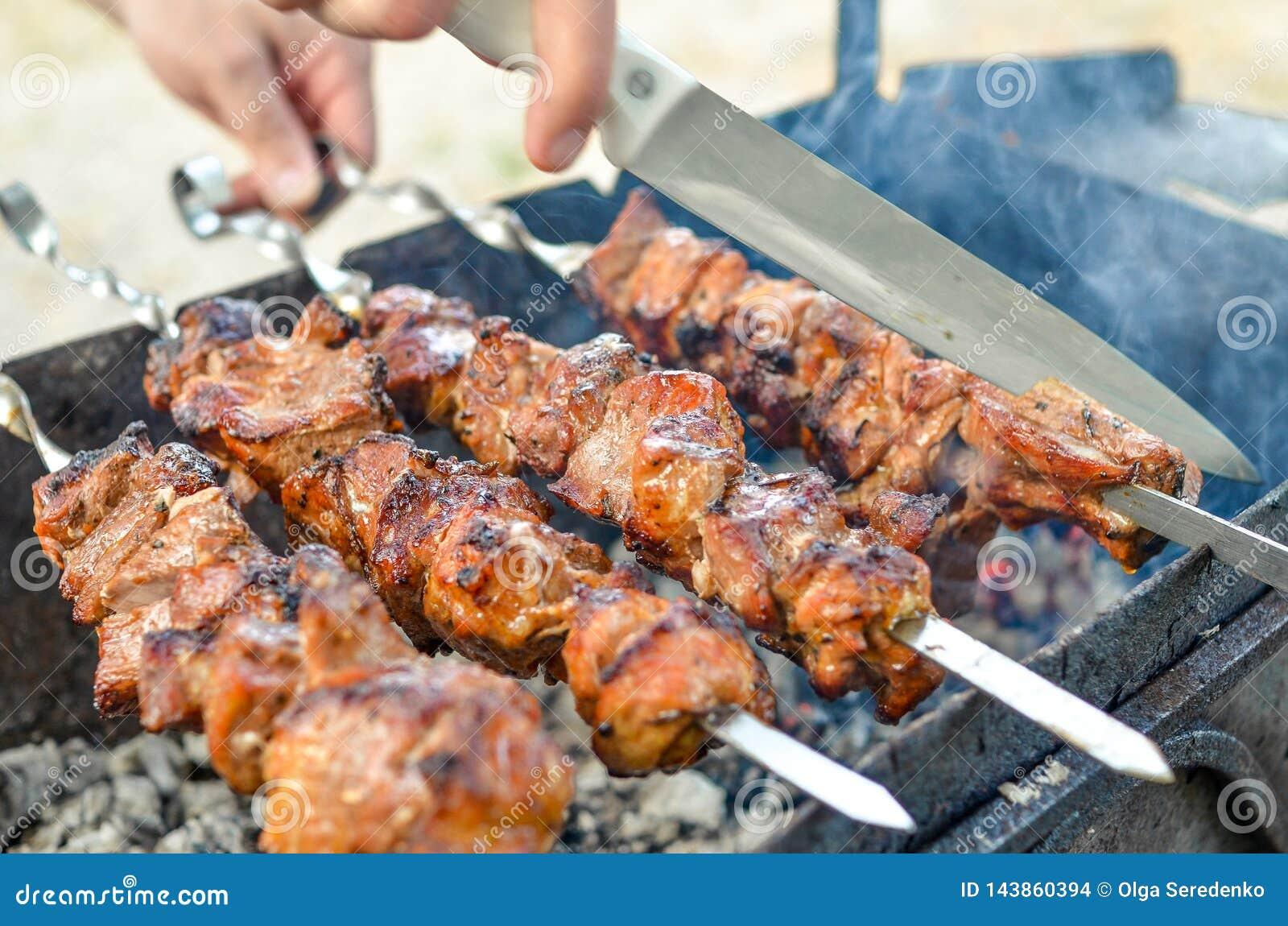 油煎在金属串的烤kebab 烤肉被烹调在与烟的烤肉 关闭