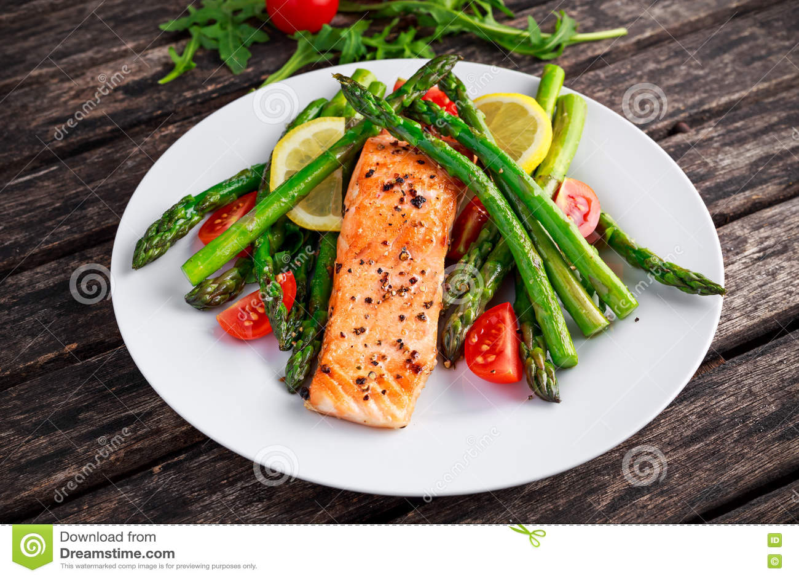 油煎的三文鱼用芦笋,蕃茄,柠檬,在白色板材的黄色石灰