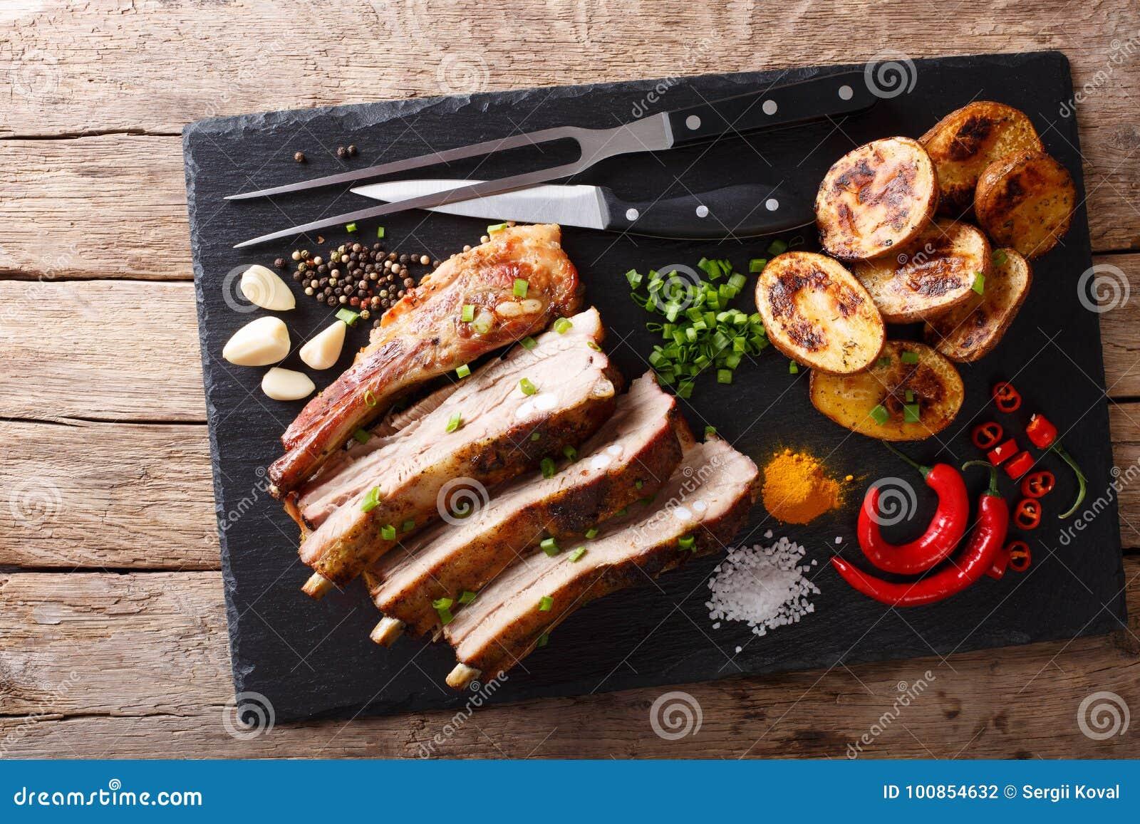 油煎的猪排用大蒜和辣椒和被烘烤的土豆