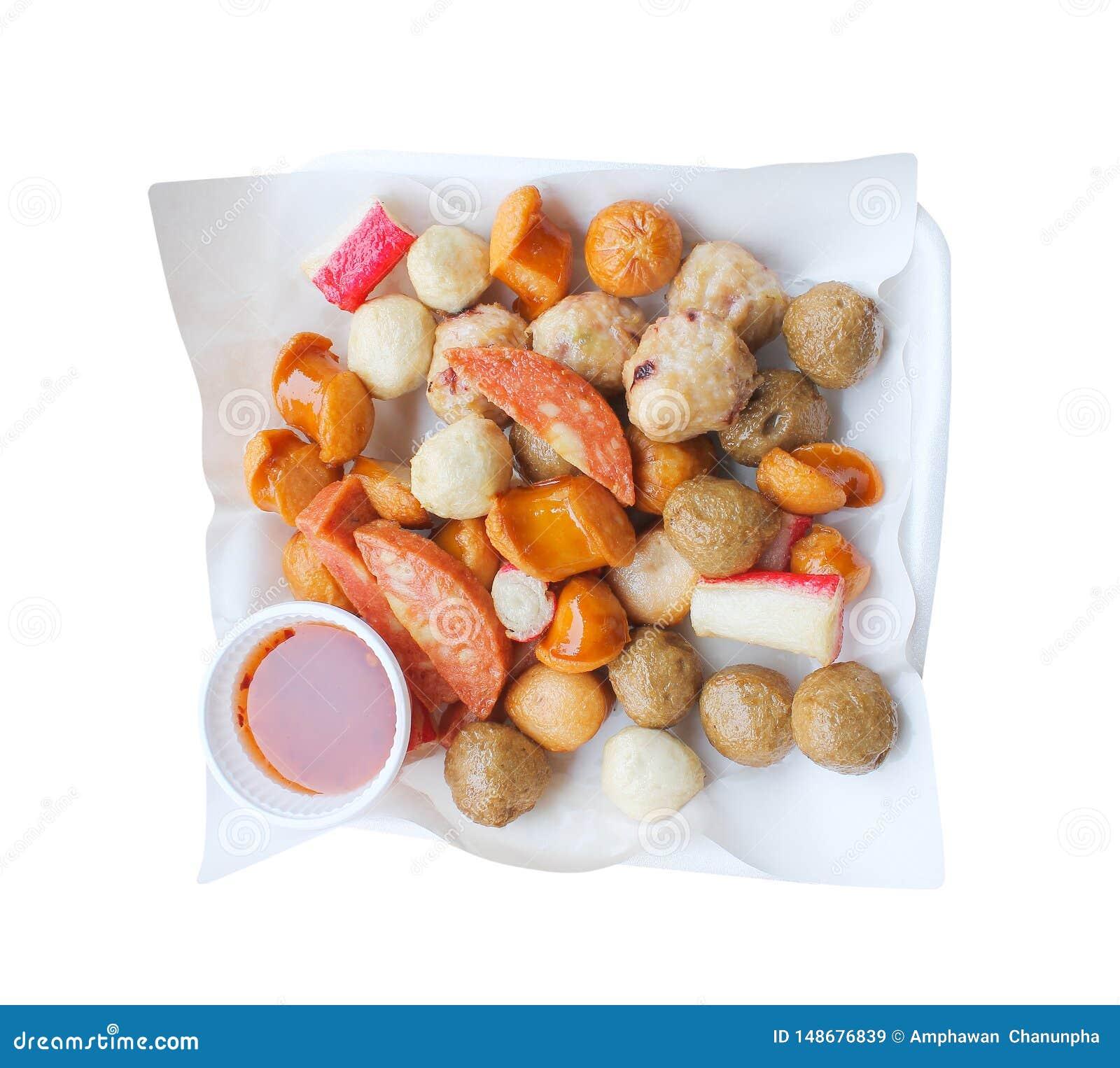油煎的猪肉和牛肉丸子,香肠,螃蟹棍子用在白色在泡沫盘子顶视图隔绝的吸墨水纸油的甜调味汁