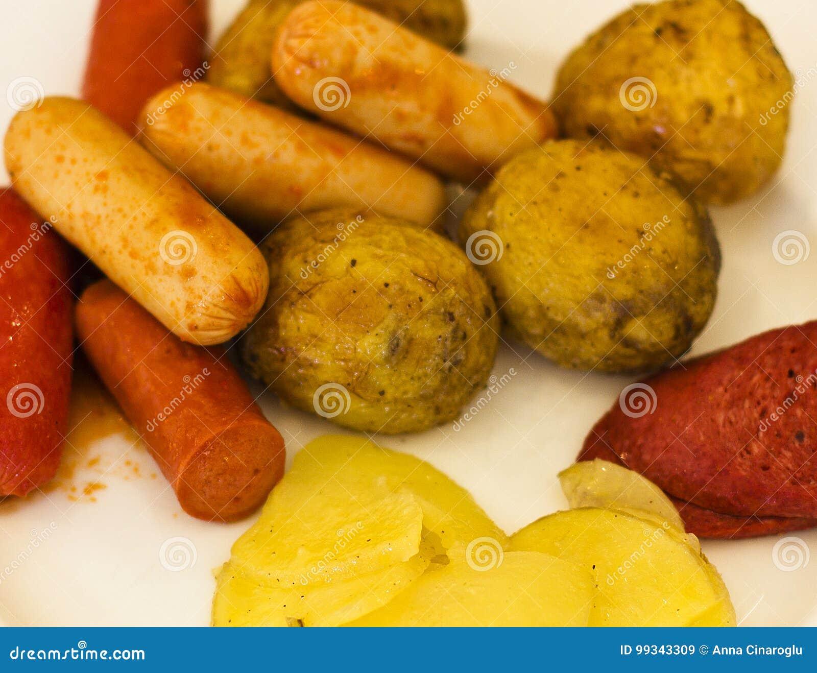 油煎的香肠用在一块白色板材的被烘烤的土豆 有选择性的f