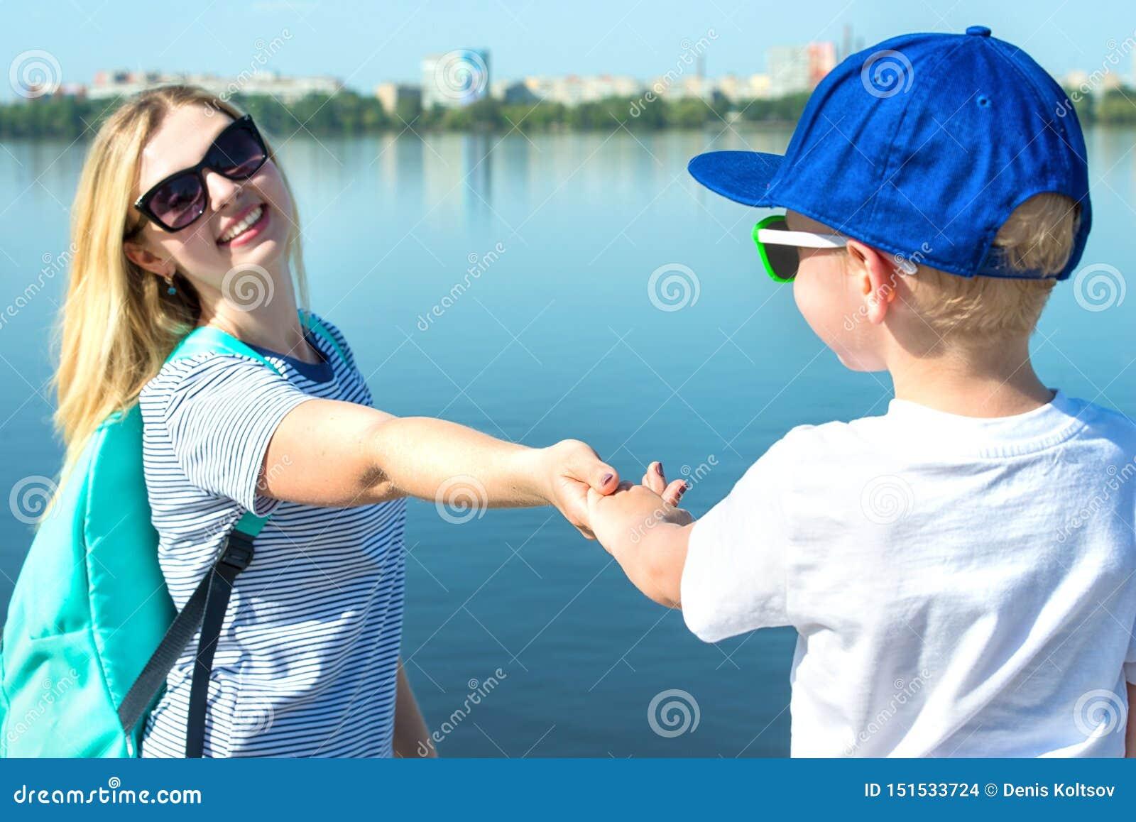 沿散步的母亲和儿子步行和握手